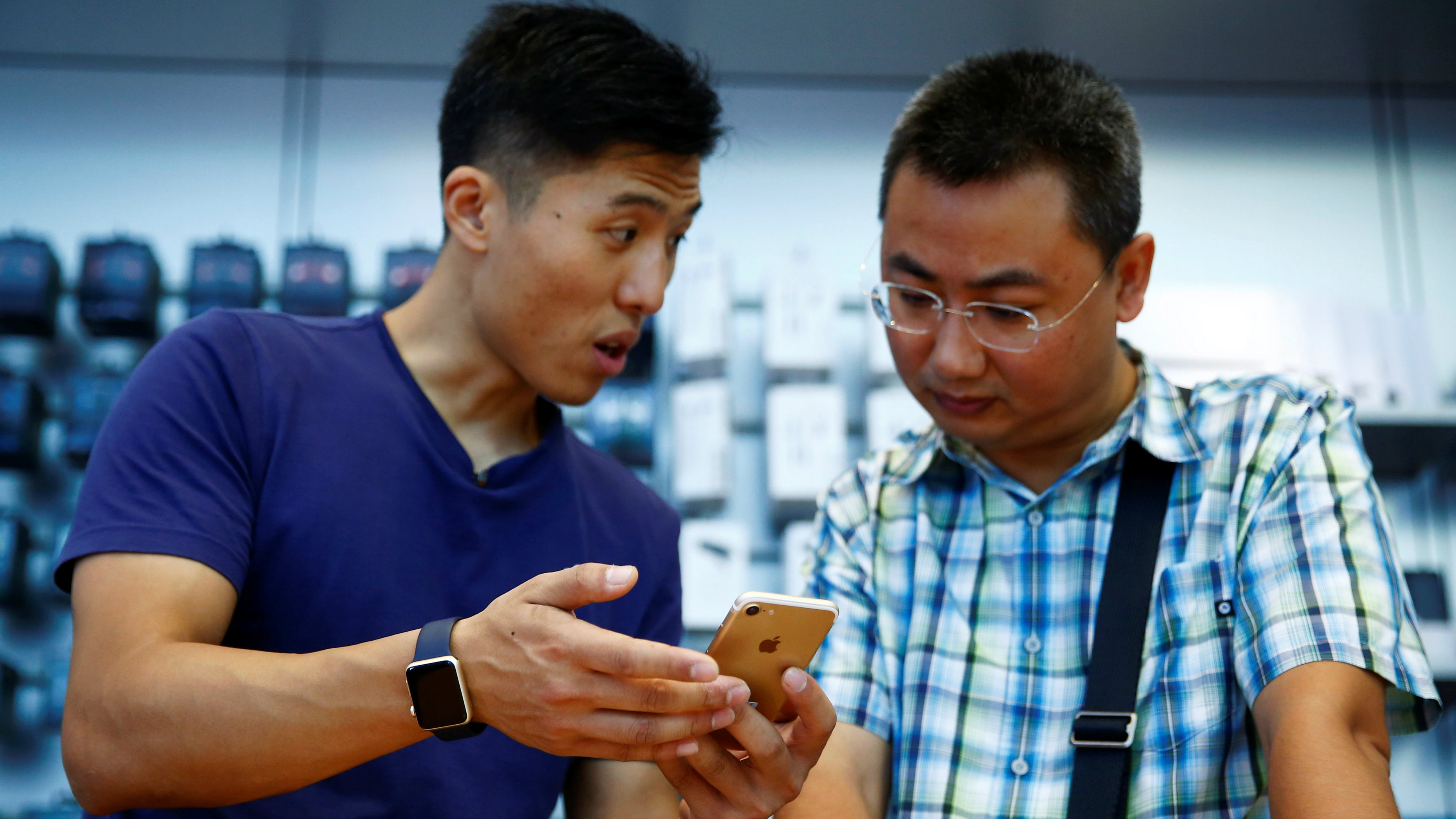 A staff member (L) explains Apple's new iPhone 7 to a customer at an Apple store in Beijing, China