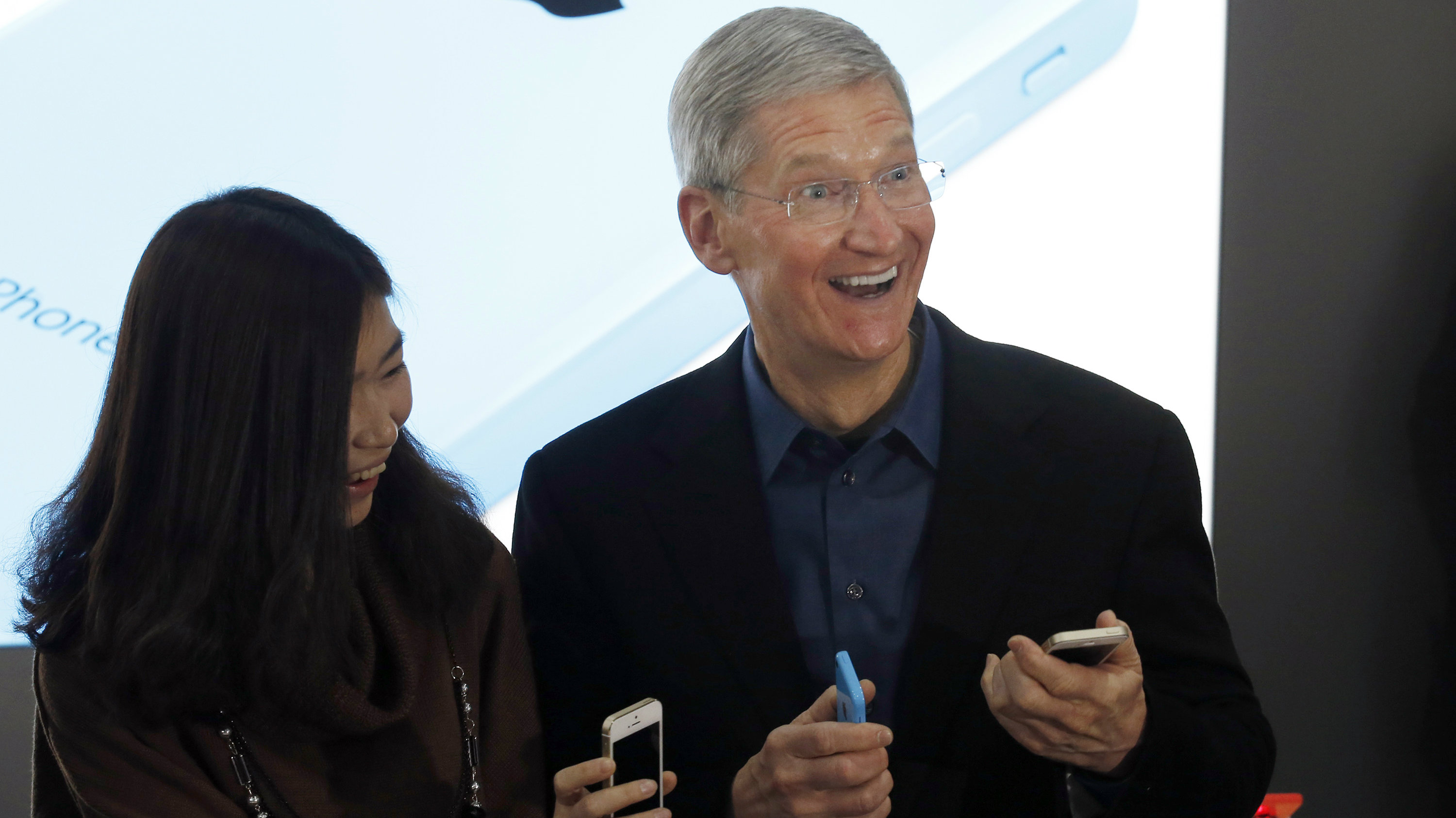 Apple Inc. CEO Tim Cook reacts as he shows his iPhones while posing with a customer at an event celebrating the launch of Apple's iPhone on China Mobile's network at a China Mobile shop in Beijing January 17, 2014. Apple Inc is finally launching its iPhone on China Mobile Ltd's vast network on Friday, opening the door to the world's largest carrier's 763 million subscribers and giving its China sales a short-term jolt.