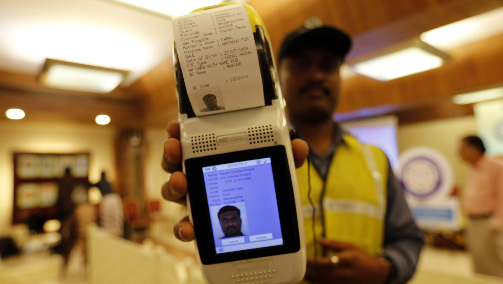 A state-owned bank officer displays a portable machine that aids in easy opening of bank accounts, during the launch of a countrywide campaign to open millions of accounts for the poor in Mumbai, India, Thursday, Aug. 28, 2014. The measure is aimed at some 150 million Indians who are off the financial grid and vulnerable to black market money lenders. As an incentive the federal government is providing 100,000 rupees ($1,650) in life insurance to every account holder.