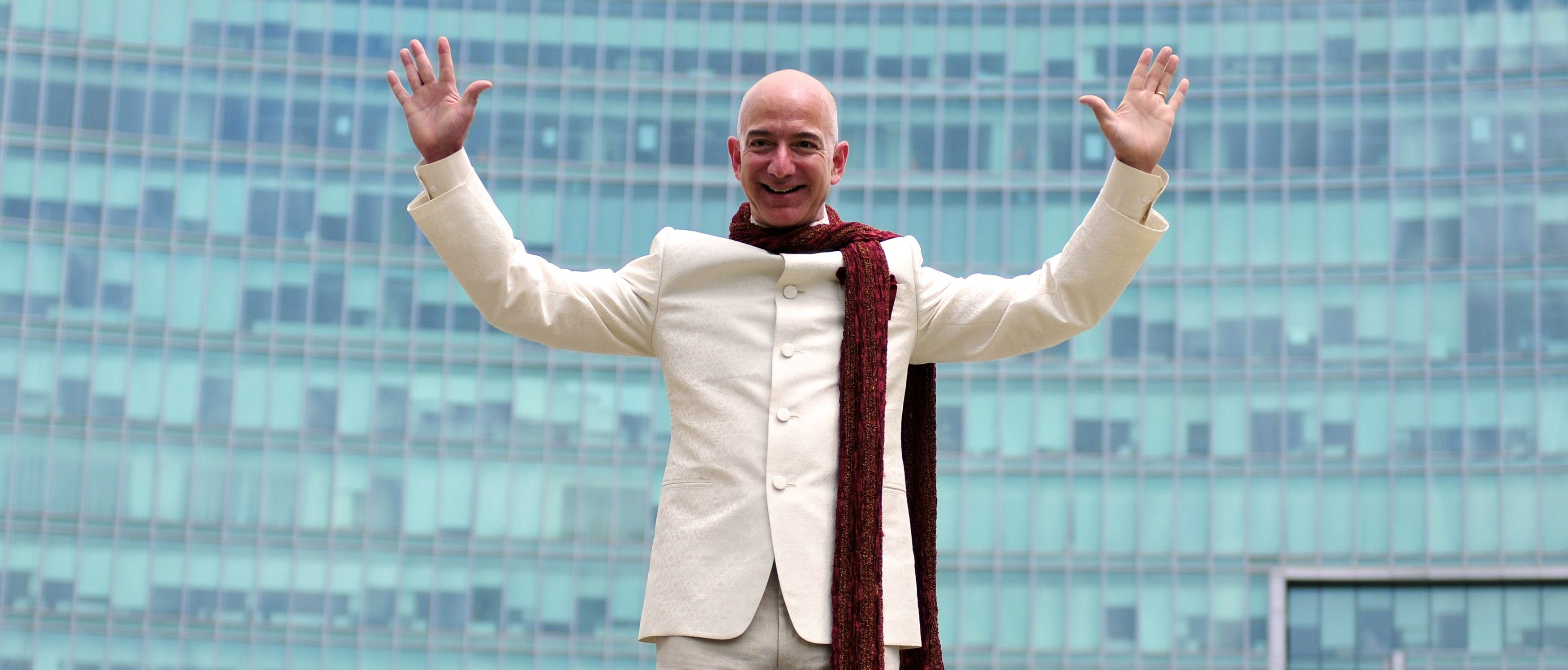Jeff Bezos, founder and chief executive officer of Amazon, poses as he stands atop a supply truck during a photo opportunity at the premises of a shopping mall in the southern Indian city of Bangalore September 28, 2014.
