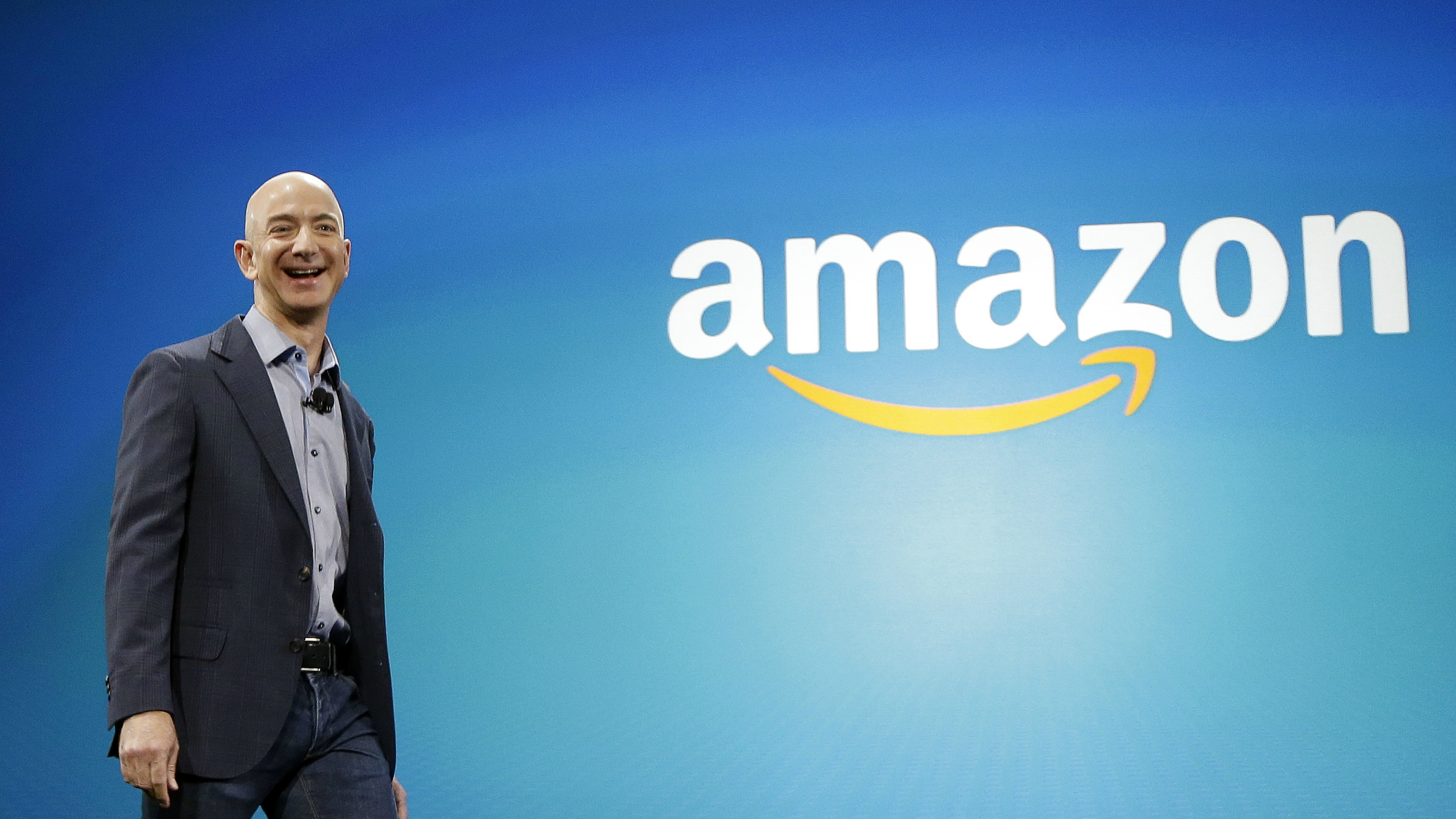 Jeff Bezos in front of an Amazon sign.