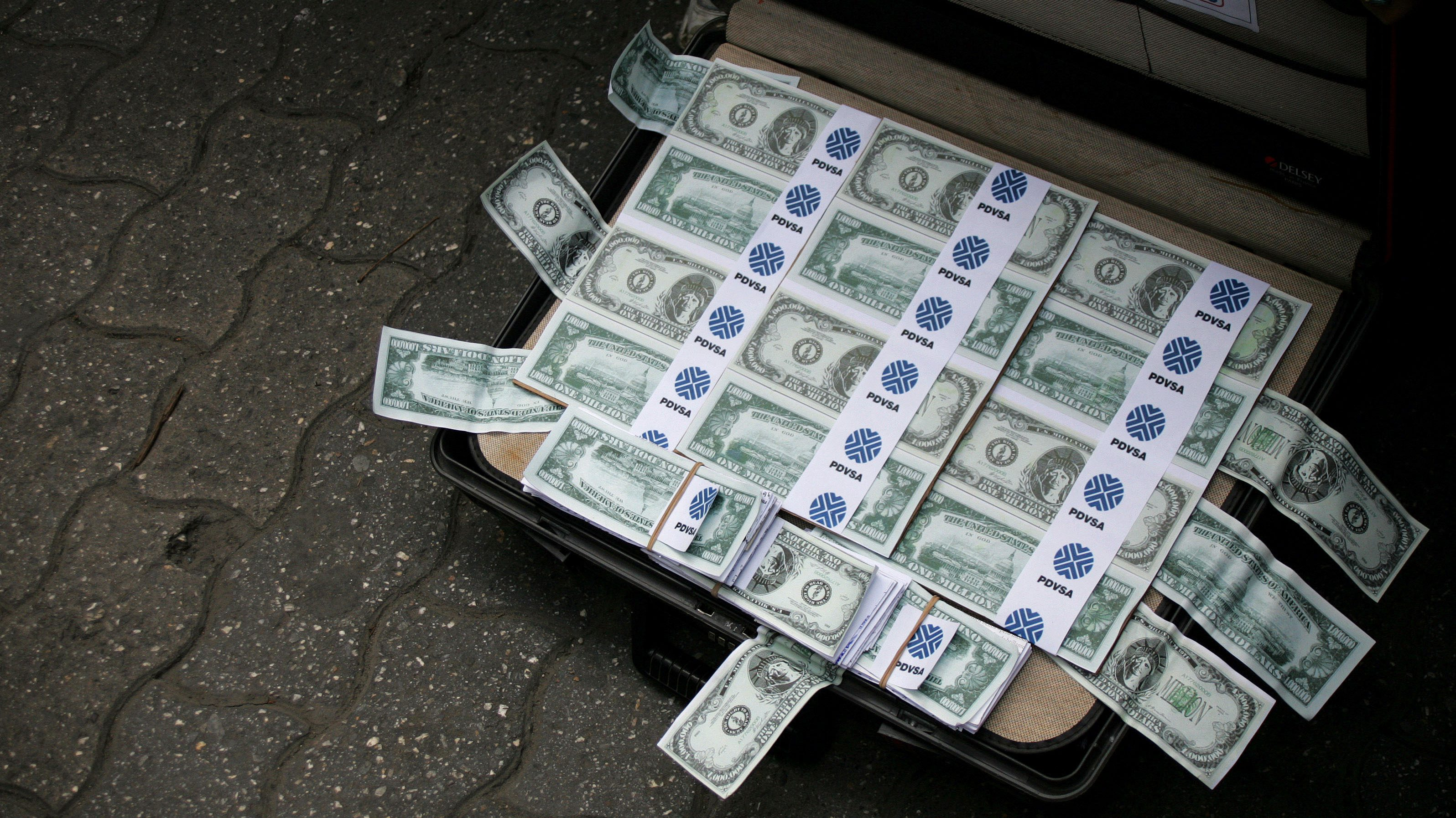 A suitcase full of counterfeit money lies on the floor during a protest in Caracas August 15, 2007. Venezuelan state oil company PDVSA is investigating how a suitcase with nearly $800,000 in undeclared cash ended up on a plane carrying company officials to Argentina to work on bilateral cooperation deals. The incident prompted the resignation of an official in Argentine President Nestor Kirchner's government and has embarrassed Venezuela's Hugo Chavez, who travelled earlier this week to Buenos Aires to discuss energy accords with his leftist counterpart.