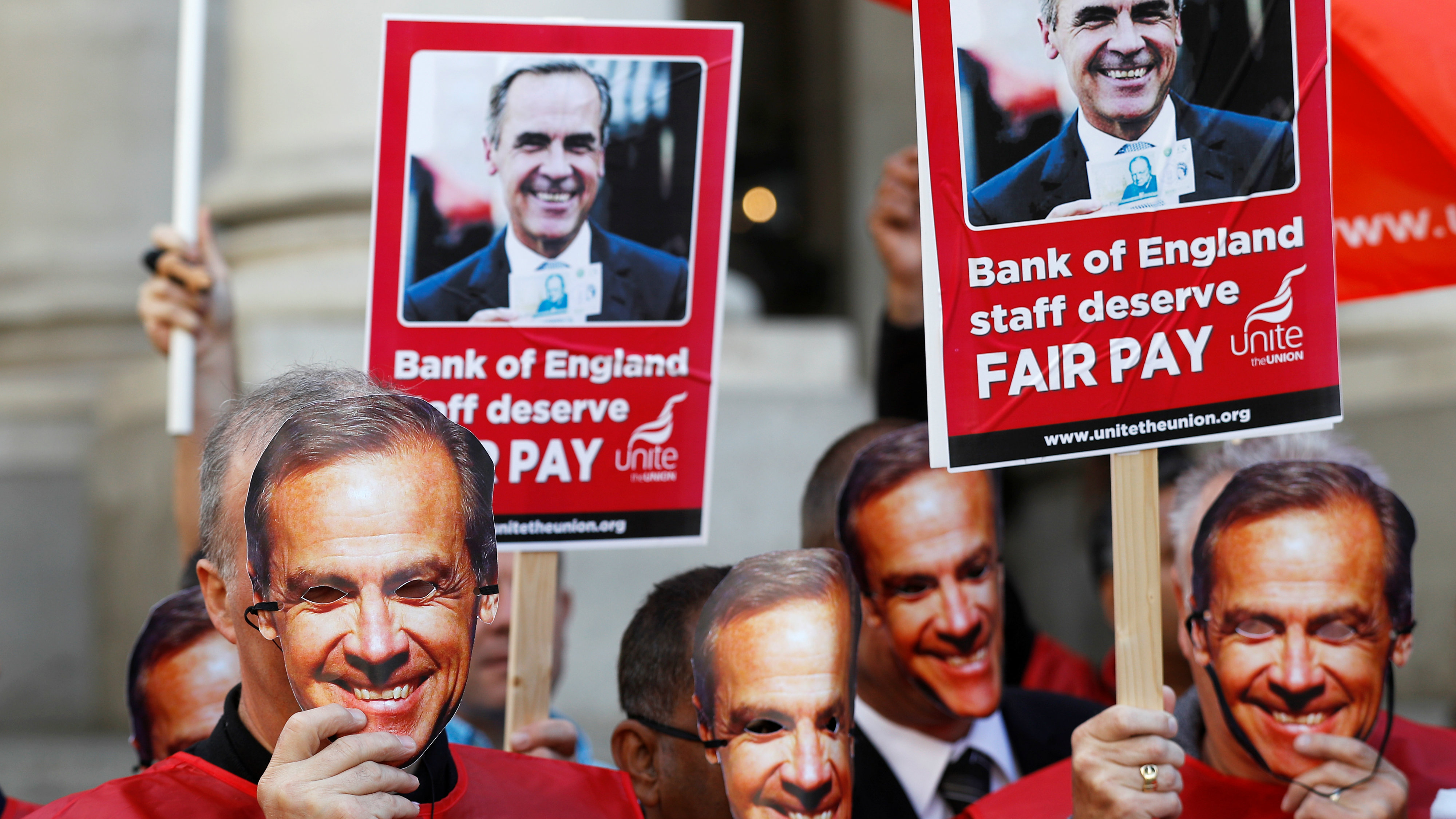 Protesters hold up Bank of England Governor Mark Carney masks outside the bank as it staff begins a three day strike over pay