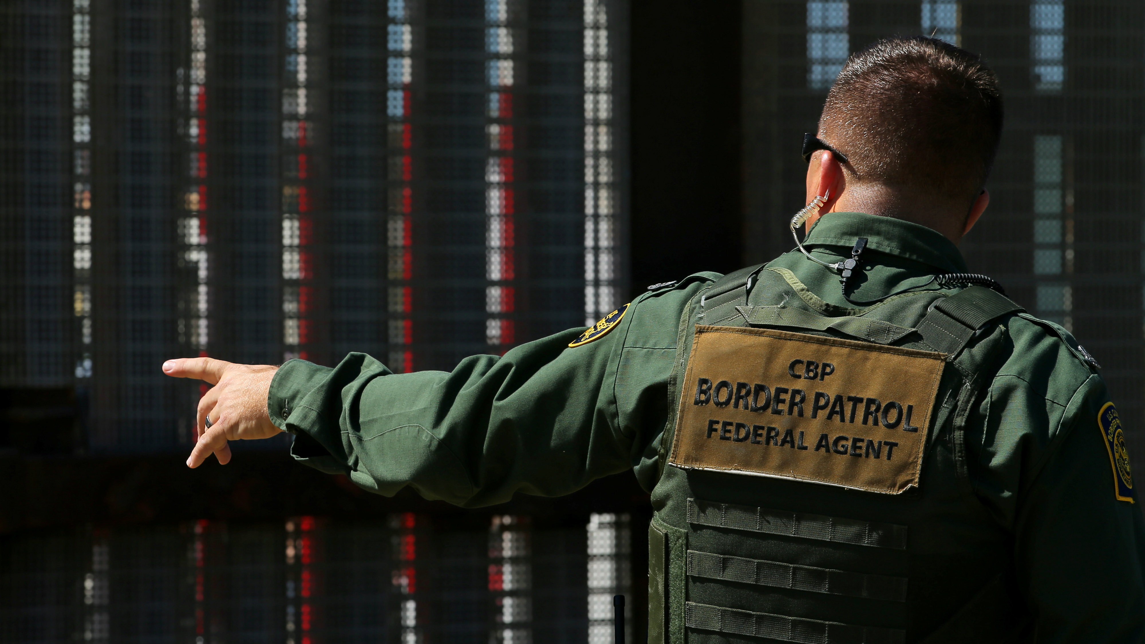 A border patrol officer next to the Mexico-US border.