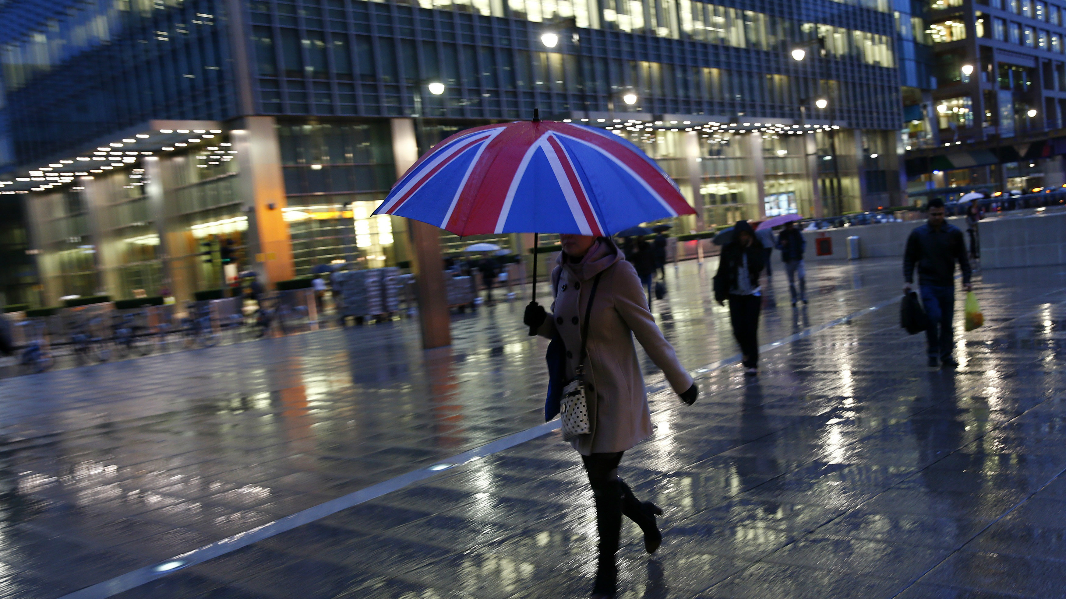Workers walk in the rain at the Canary Wharf business district in London November 11, 2013. London's financial services sector created 25 percent more jobs in February than a year ago, new data has shown, indicating the industry may be recovering from the restructuring and redundancies prompted by the financial crisis. After a strong January, the City hiring market showed no signs of slowing down last month, with 3,220 new jobs created, compared with 2,575 added in February 2013, according to financial services recruiter Astbury Marsden. The data suggests London's banks and financial services companies are returning to growth after slashing thousands of jobs in the face of a lengthy recession and a series of industry scandals that followed the financial crisis. Picture taken November 11, 2013.