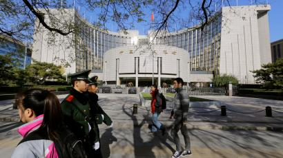 People walk past the headquarters of the People's Bank of China (PBOC), the central bank, as two paramilitary police officials patrol around it in Beijing November 20, 2013.