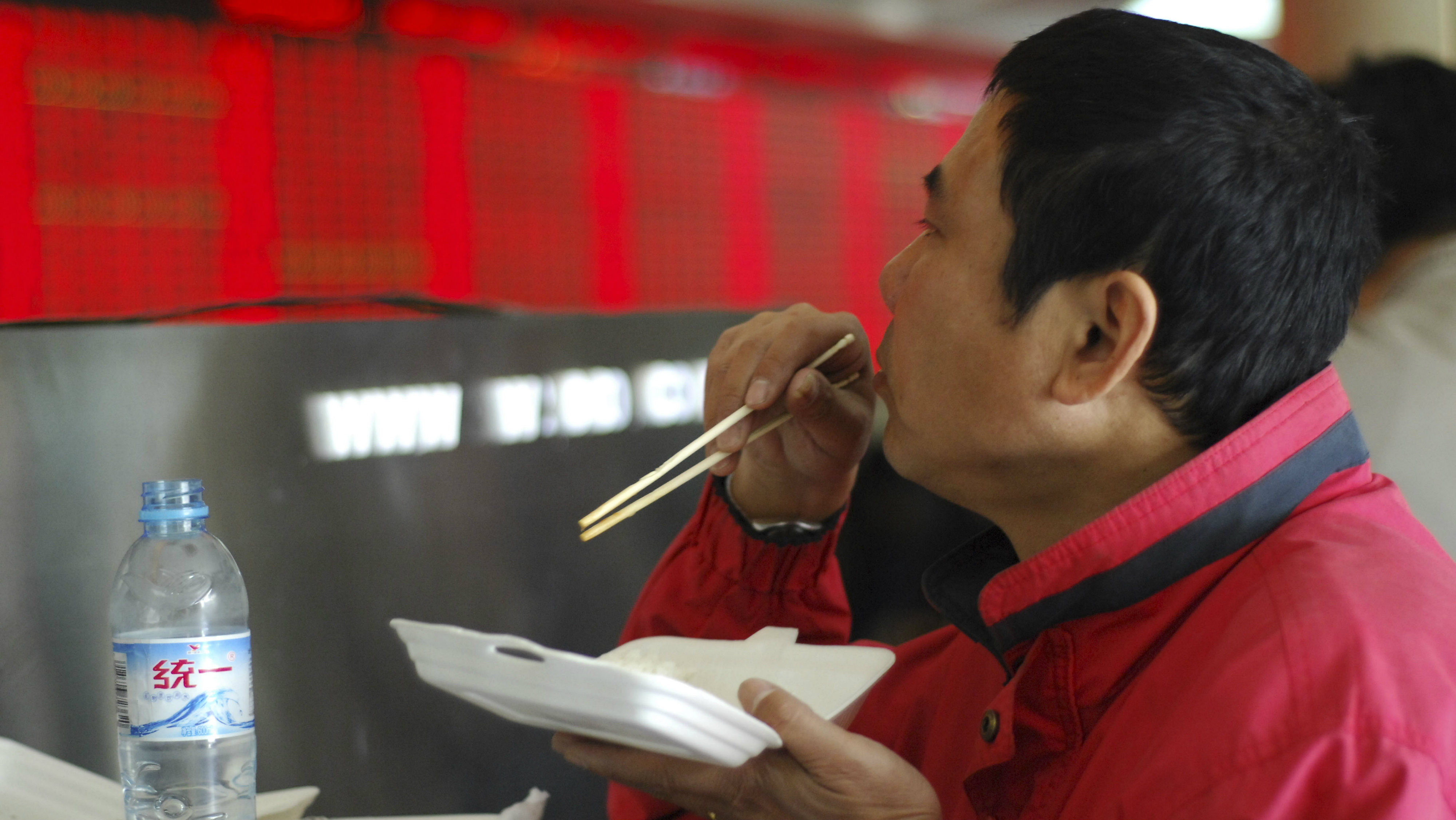 An investor eats before an electronic board in a brokerage hall in Shanghai April 24, 2008. China's main stock index soared over 7 percent in frenzied trade on Thursday after the government cut the share trading tax, seeking to end a bear market that had slashed stock prices by half in six months.