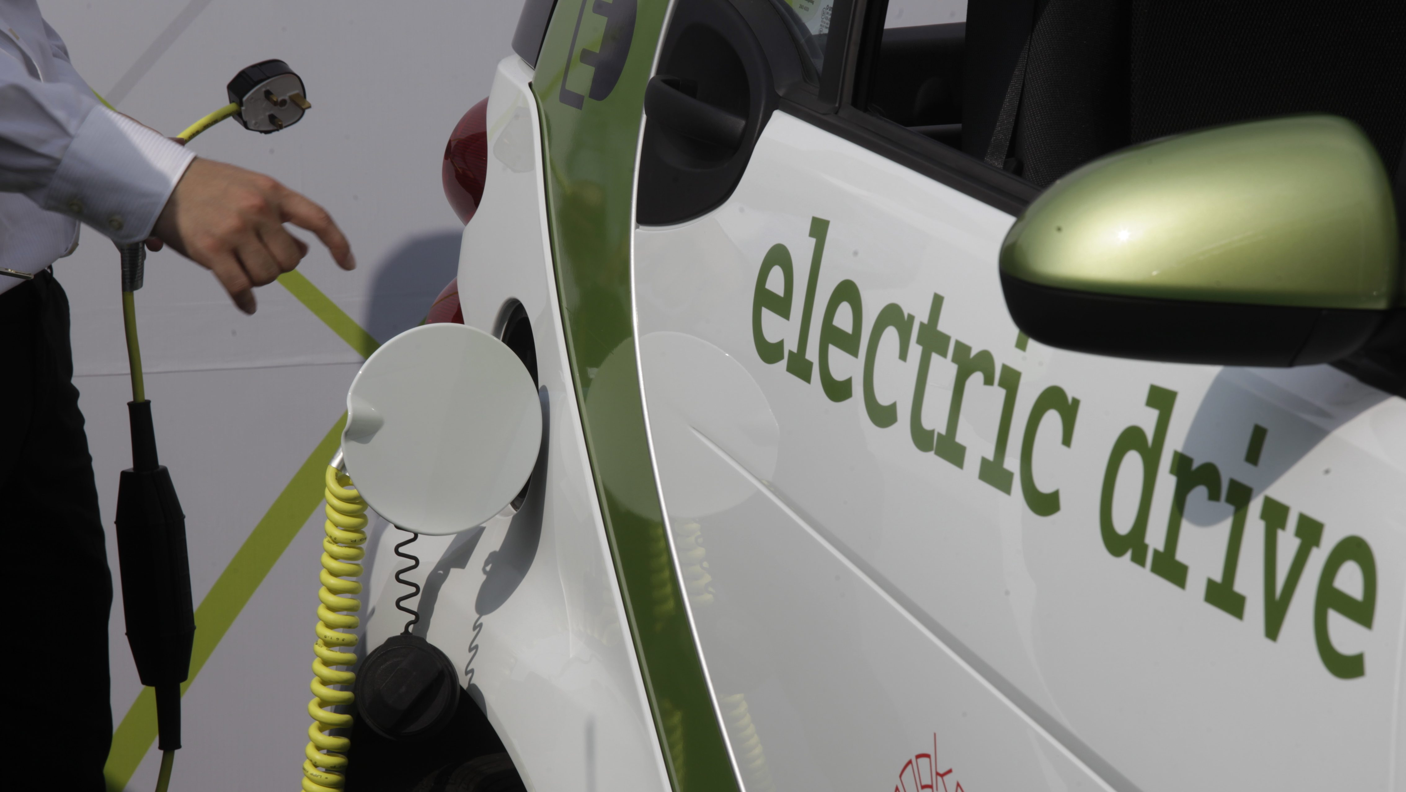 A man holds an electric socket beside a Mercedes-Benz Smart Fortwo electric vehicle during its official launch ceremony in Hong Kong, China, 06 September 2011. Smart Fortwo electric vehicle is the first European electric vehicle for daily use in Hong Kong. The two-seater, which is powered by a 30 kw electric motor fitted at the rear, runs a top speed of 100mph.