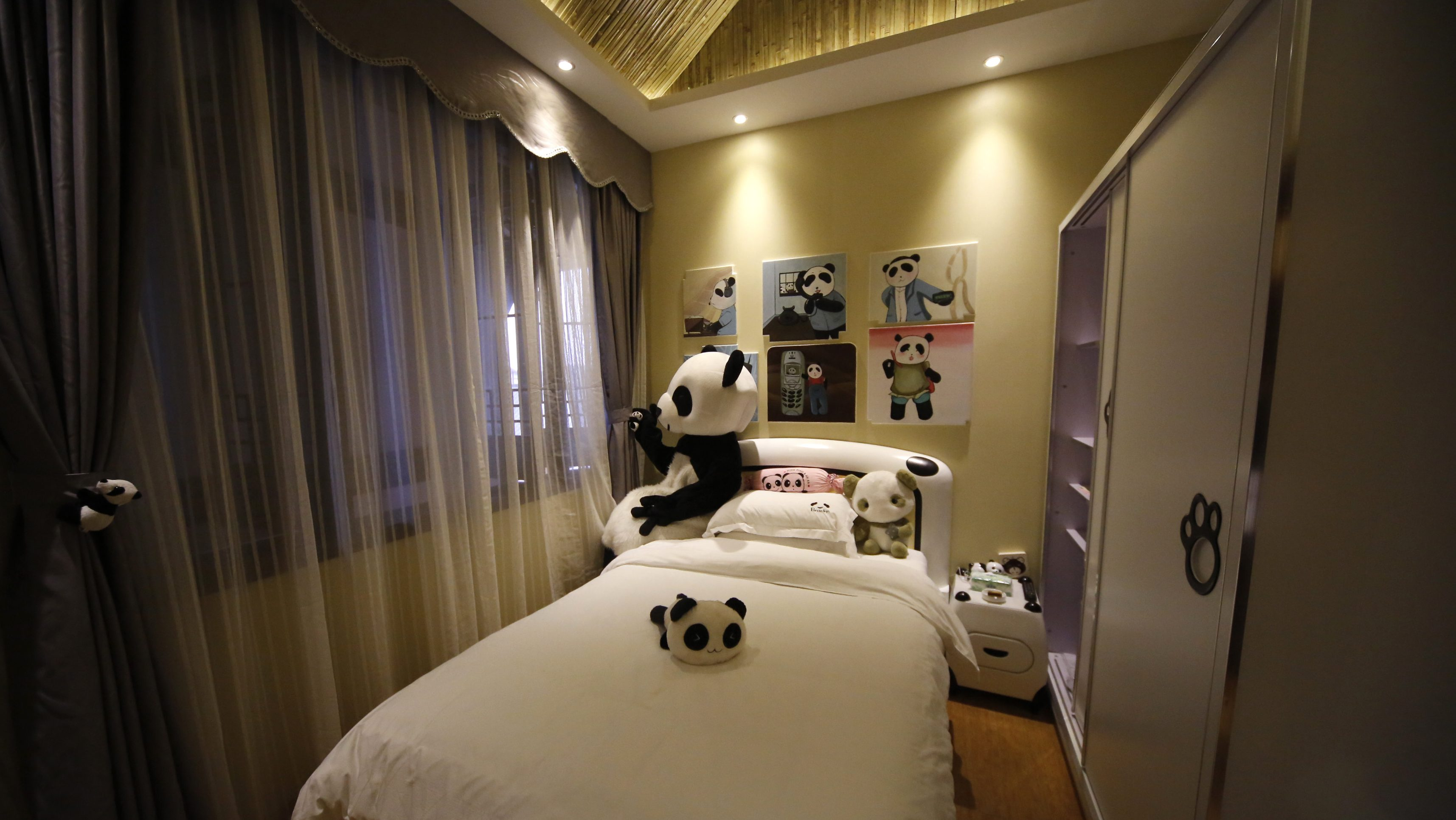 An employee dressed in a panda costume poses for a photo during the soft opening of a panda-themed hotel at the foot of Emei Mountain, Southwest China's Sichuan province, February 25, 2013. According to local media, the hotel is the first panda-themed hotel in the world and will officially open in May with room rates from 300 to 500 yuan ($48 to $80) per night. Picture taken February 25, 2013. REUTERS/China Daily (CHINA - Tags: ANIMALS SOCIETY) CHINA OUT. NO COMMERCIAL OR EDITORIAL SALES IN CHINA - GM1E92Q1RGO01