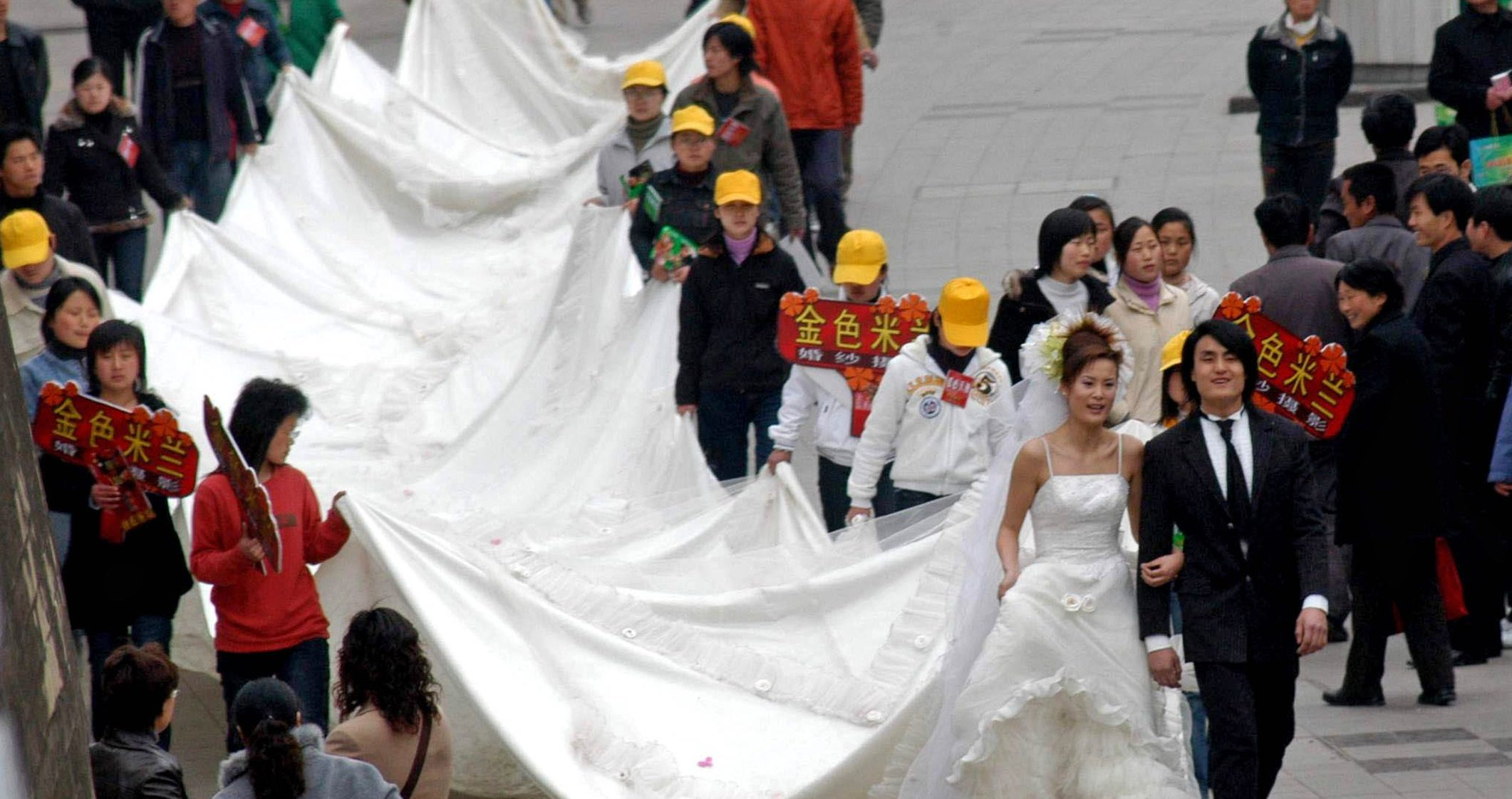 Chinese pedestrians watch a model wearing a 50-metre-long wedding gown on a street in Hefei, east China's Anhui province March 19, 2005. China saw 1.613 million couples divorce in 2004, an increase of 21.2 percent over the previous year, according the Ministry of Civil Affairs.