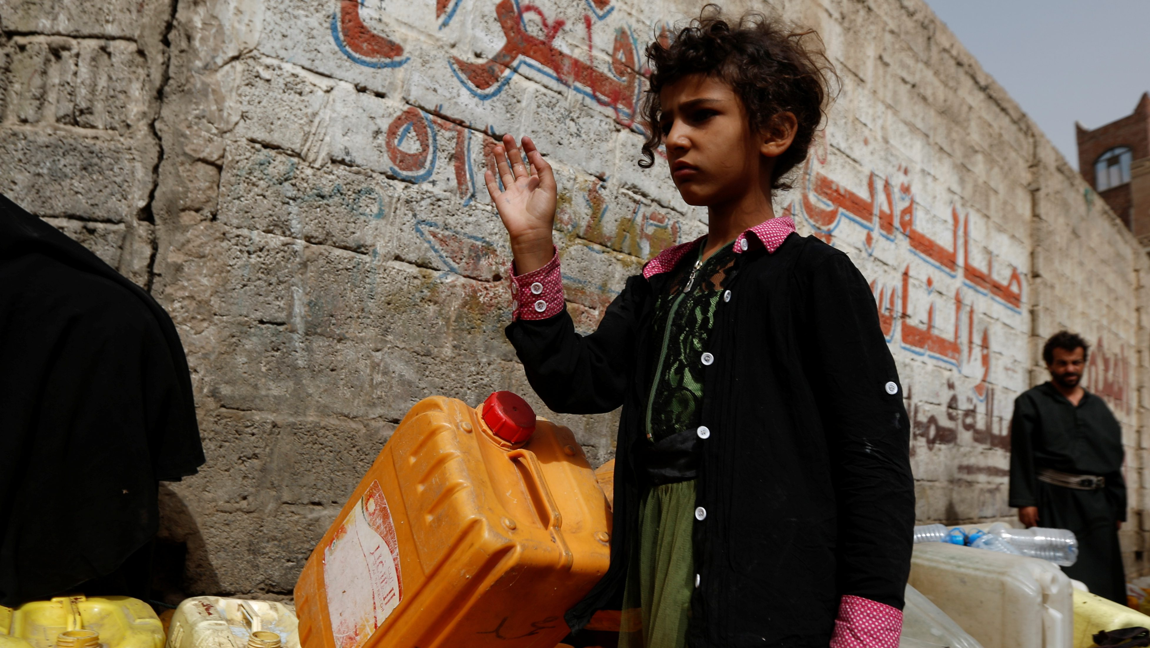 A girl stands by water cans on a street where a charity tanker truck delivers free drinking water in Sanaa, Yemen, July 10, 2017. A  cholera outbreak caused by collapsed water and sanitation systems is growing worse.