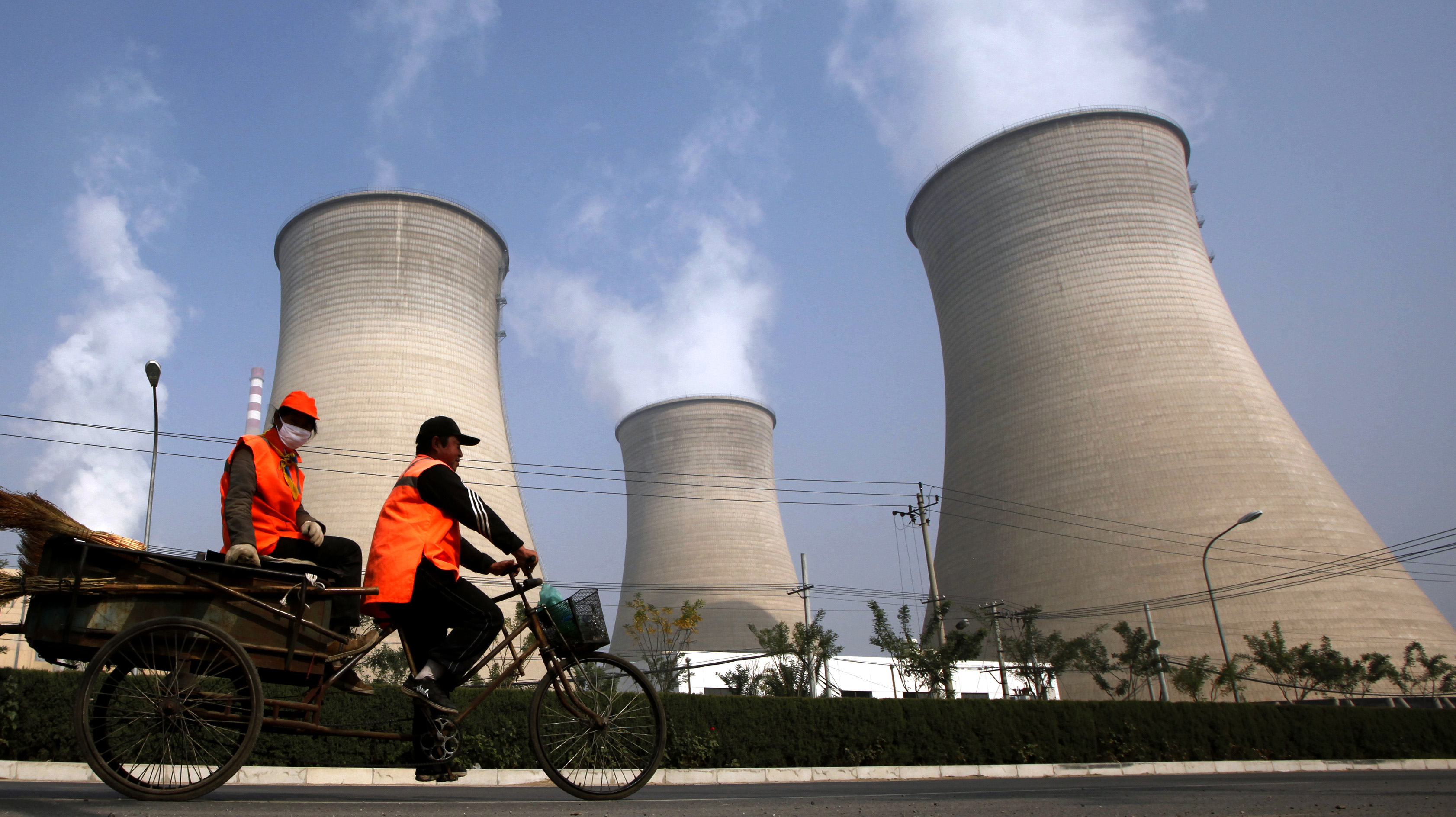 Street cleaners ride their motorised tricycles past the chimneys of a power station located on the outskirts of Beijing October 29, 2009. China is on track to build its first commercial-scale power plant that can capture and store emissions, but experts say it must speed up research on where and how to sequester carbon. China is the world's biggest emitter of the greenhouse gasses that cause global warming and is under increasing pressure to agree to curb output. But coal is China's most plentiful domestic source of energy, and the government hopes for decades of rapid economic expansion to lift millions more from poverty, so capturing and storing carbon dioxide is likely to be crucial to any reduction.      REUTERS/David Gray       (CHINA POLITICS ENVIRONMENT) - GM1E5AT10V201