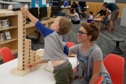 A young boy and his mom play with Learning Beautiful's binary towers at the Chicago Public Library.