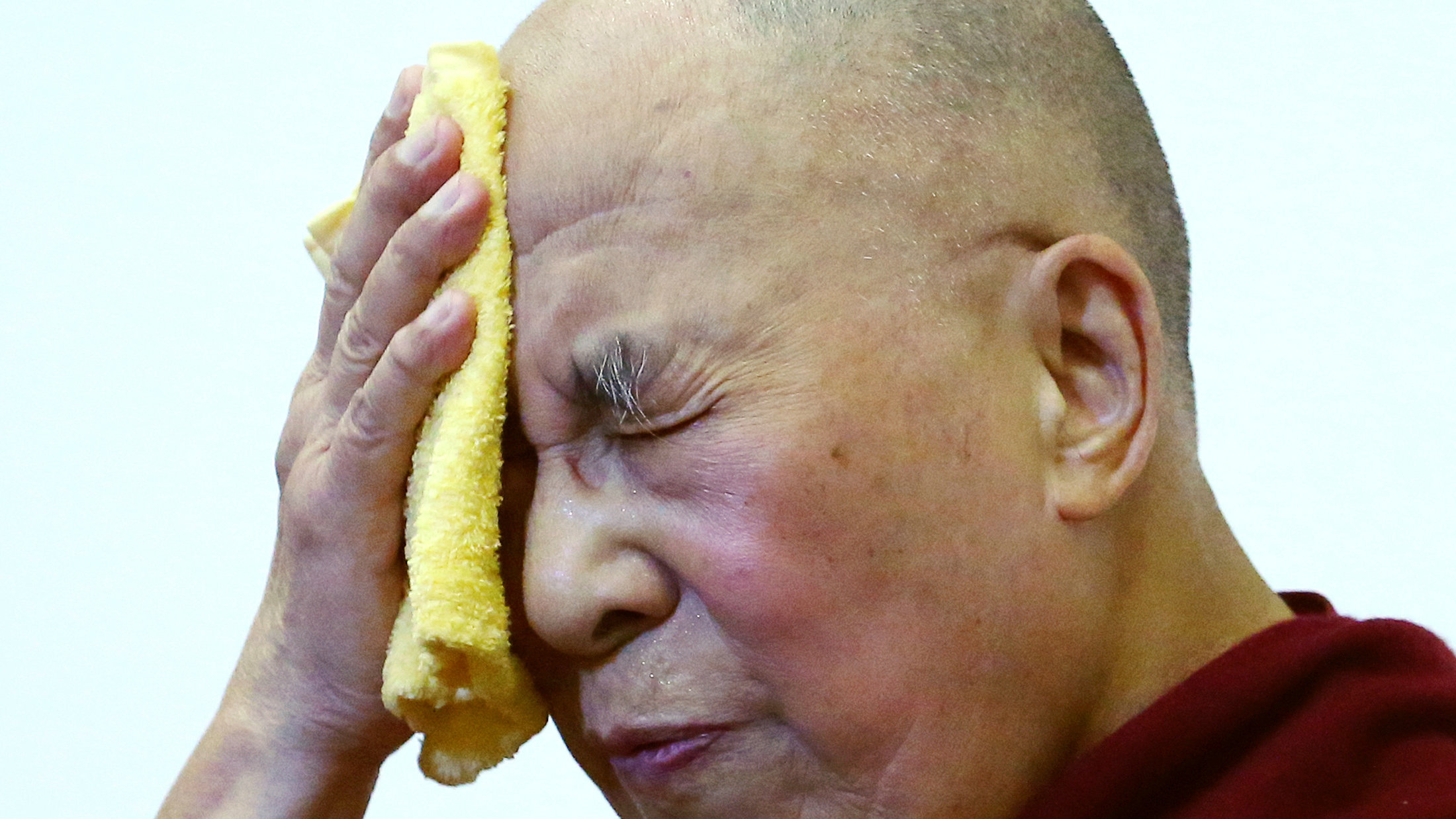 Tibet's exiled spiritual leader the Dalai Lama wipes his face during an international conference of Tibet support groups in Brussels, Belgium, September 8, 2016.