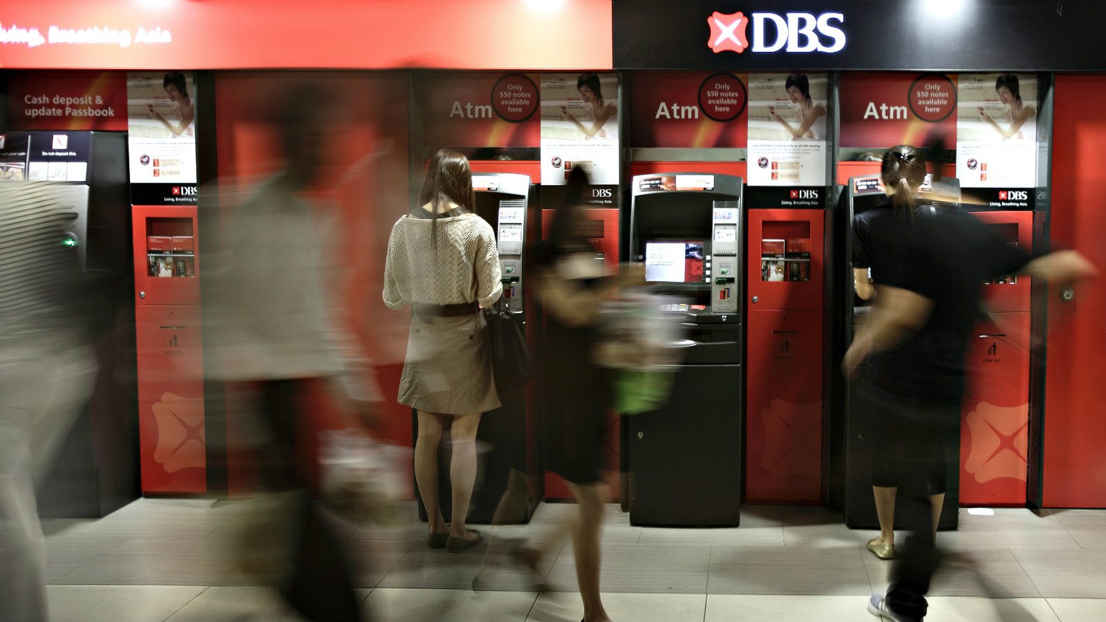 People use DBS ATMs at a subway station in Singapore