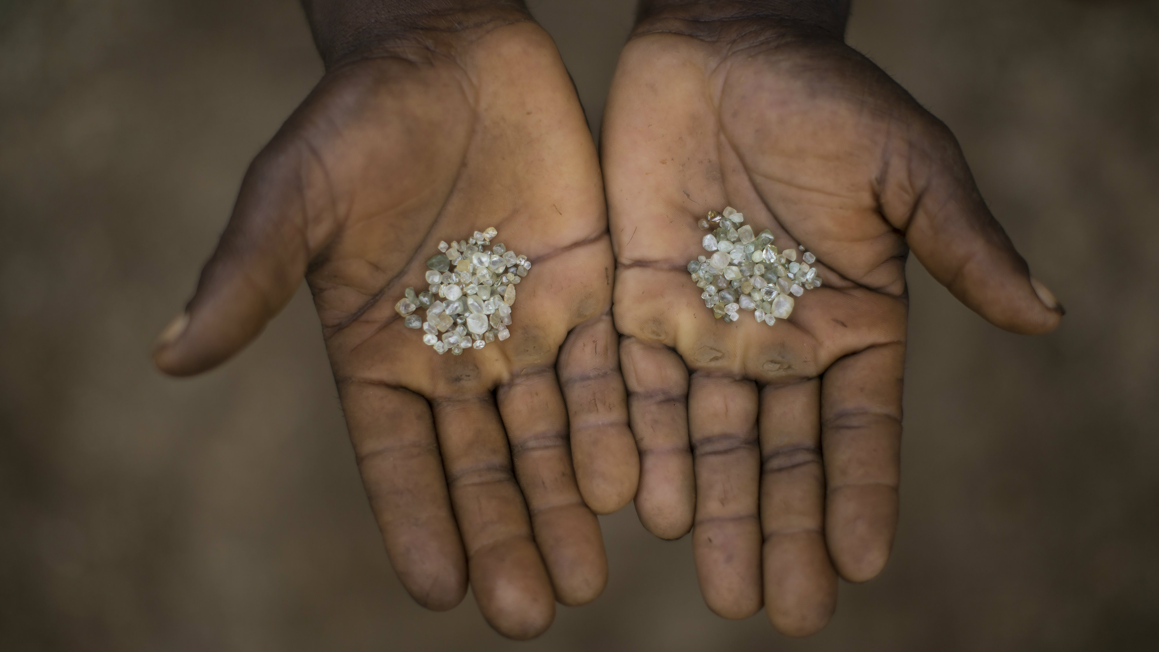 In this Nov. 19, 2015 photo, an artisanal miner shows the diamonds he and his group found in an abandoned mine in Areinha, Minas Gerais state, Brazil. The area has been explored for the precious stone since the time of slavery, and up to a couple of years ago, multinational mining companies extracted the stone without care for the land or the Jequitinhonha river that crosses the region.