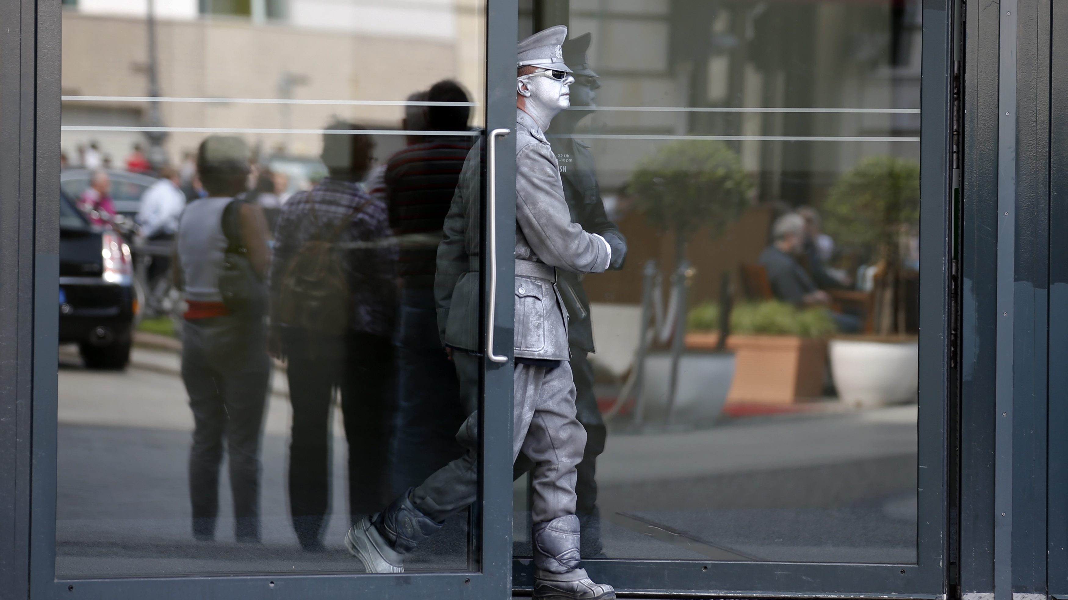 A street artist wearing a coloured uniform of the former East German army leaves the Academy of Arts near the Brandenburg Gate in Berlin, April 26, 2013.