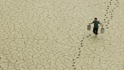 A man carrying water across a totally dried up pond.