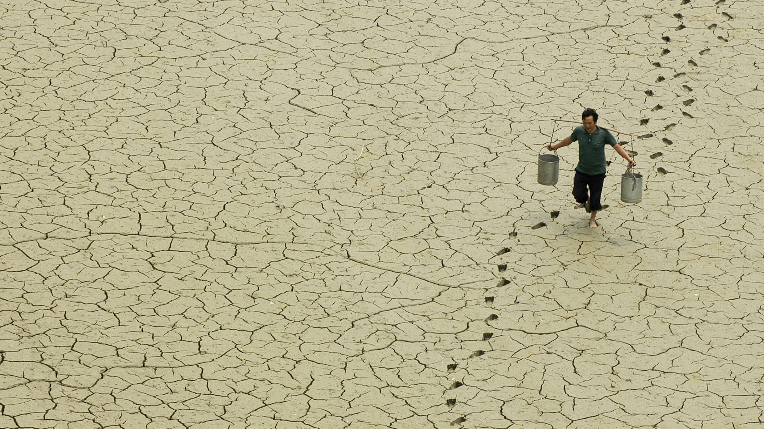 A farmer walks on a dried-up pond on the outskirts of Baokang, central China's Hubei province, June 10, 2007.