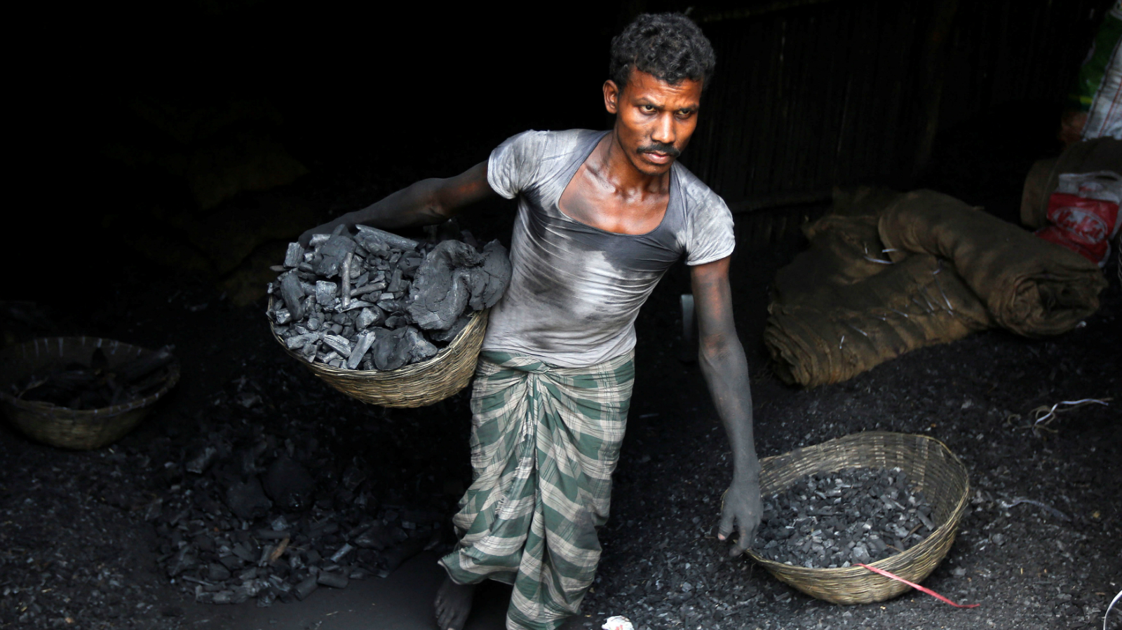 A worker carries coal in a basket in a industrial area in Mumbai, India May 31, 2017.