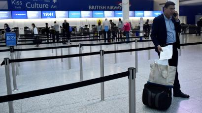 A man waits with his luggage at Gatwick Airport in southern England