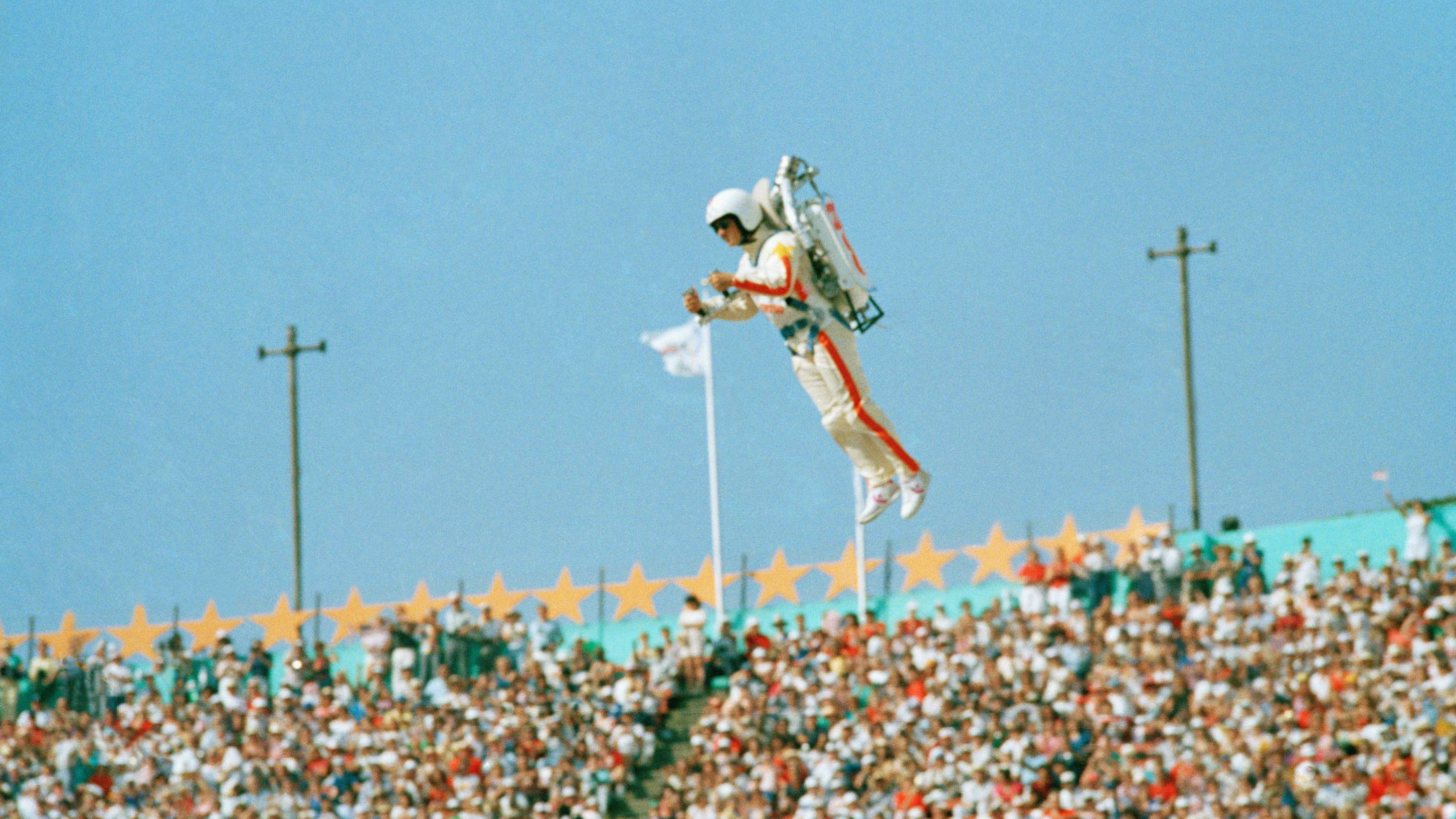 """FILE - In this July 28, 1984 file photo Bill Suiter """"Rocket Man"""" soars with the help of a jet pack during the welcoming of nations at the Opening ceremonies of the 1984 Summer Olympics in the Los Angeles Memorial Coliseum. The IOC's ruling 15-member executive board will meet Sunday, July 24, 2016 via teleconference to weigh the unprecedented step of excluding Russia as a whole from the 2016 Rio Olympic Games because of systematic, state-sponsored cheating. (AP Photo/Rusty Kennedy, file)"""