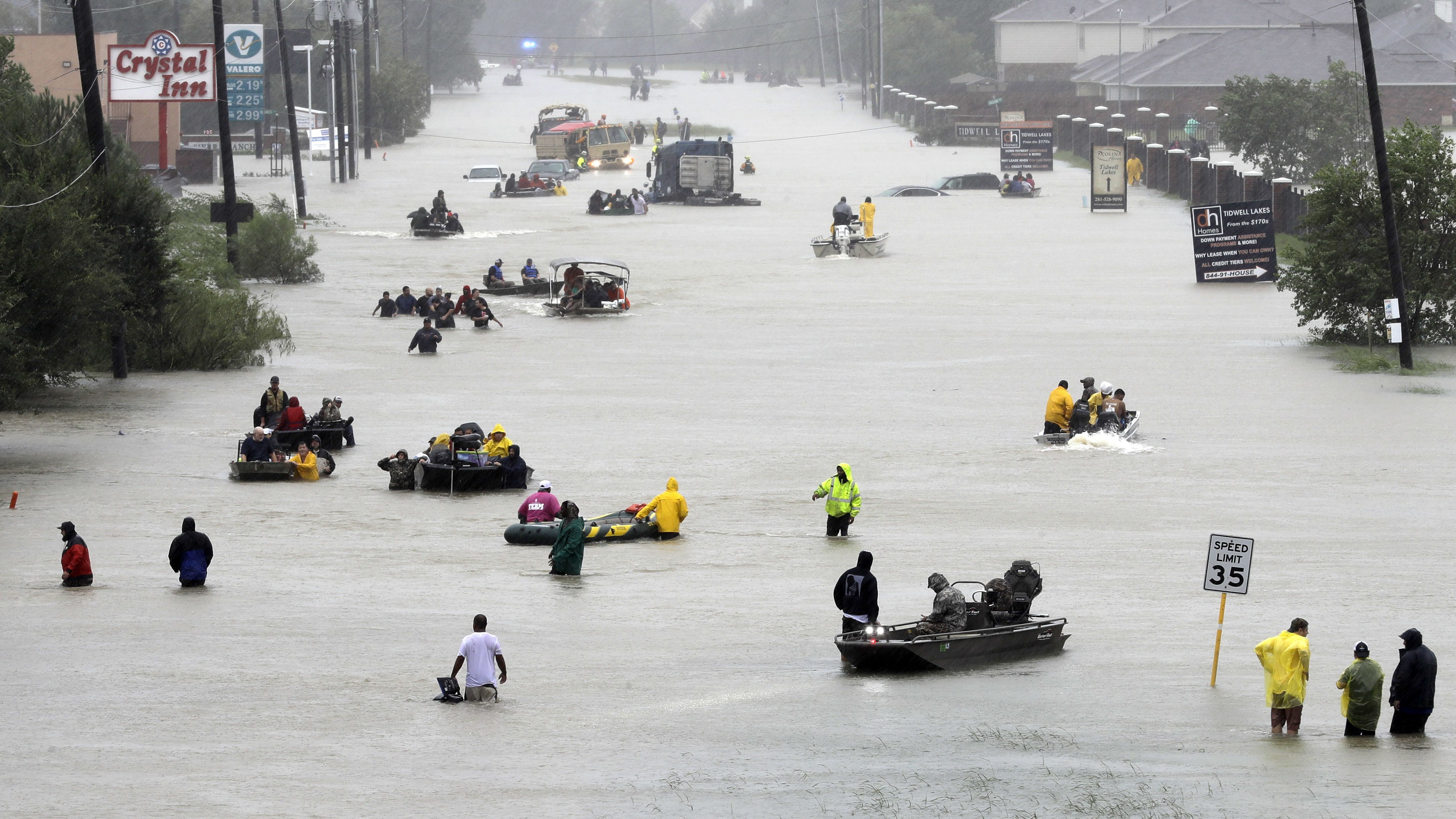 Rescue boats fill a flooded street at flood victims are evacuated as floodwaters from Tropical Storm Harvey rise Monday, Aug. 28, 2017, in Houston.