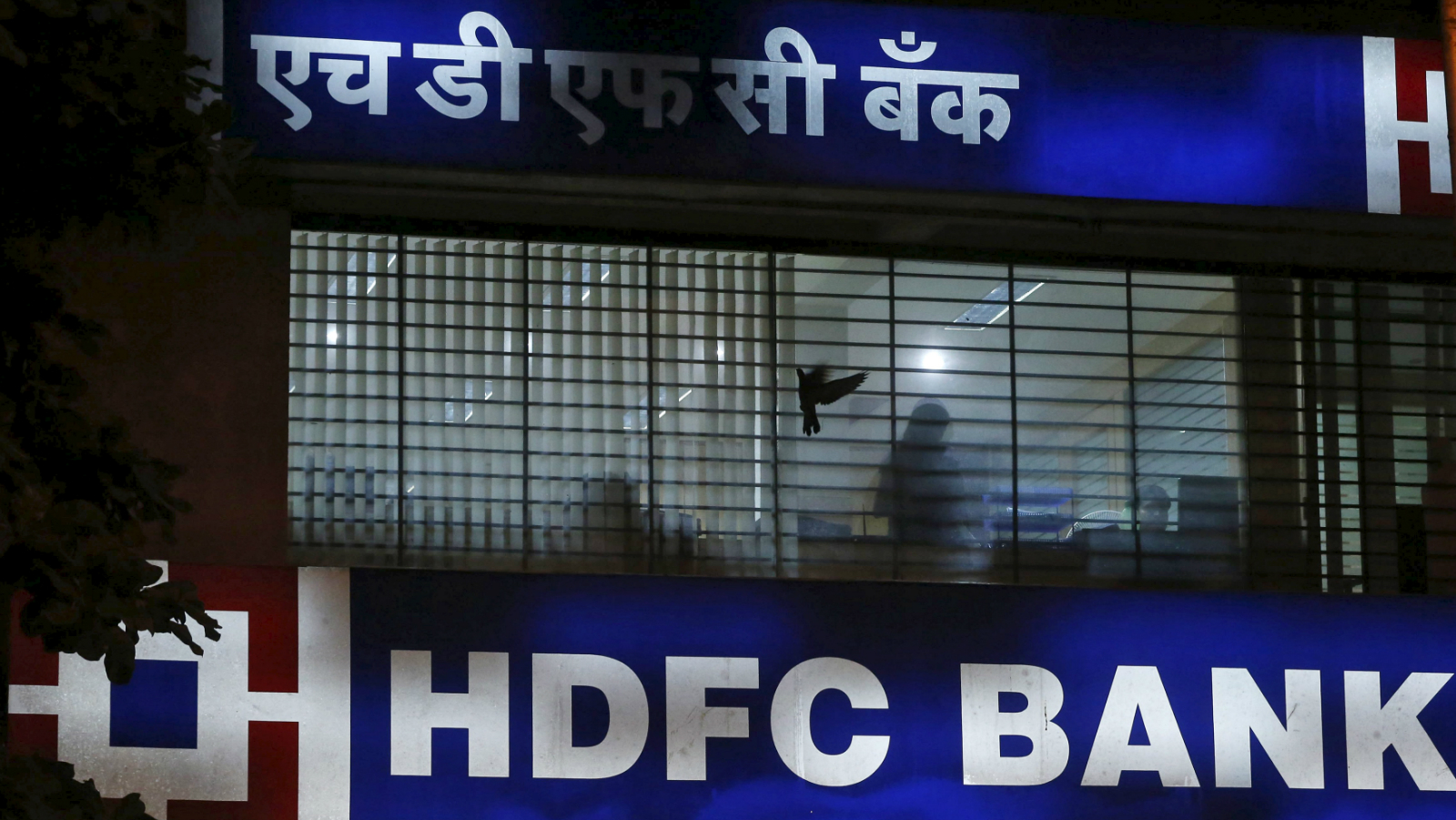 A bird flies past a window of a HDFC Bank branch office in Mumbai, India, October 21, 2015. HDFC Bank Ltd, India's second-largest private sector lender by assets, grew loans faster than expected in the second quarter as more people borrowed to buy cars and homes, making up for a slower pickup in big-ticket corporate credit.