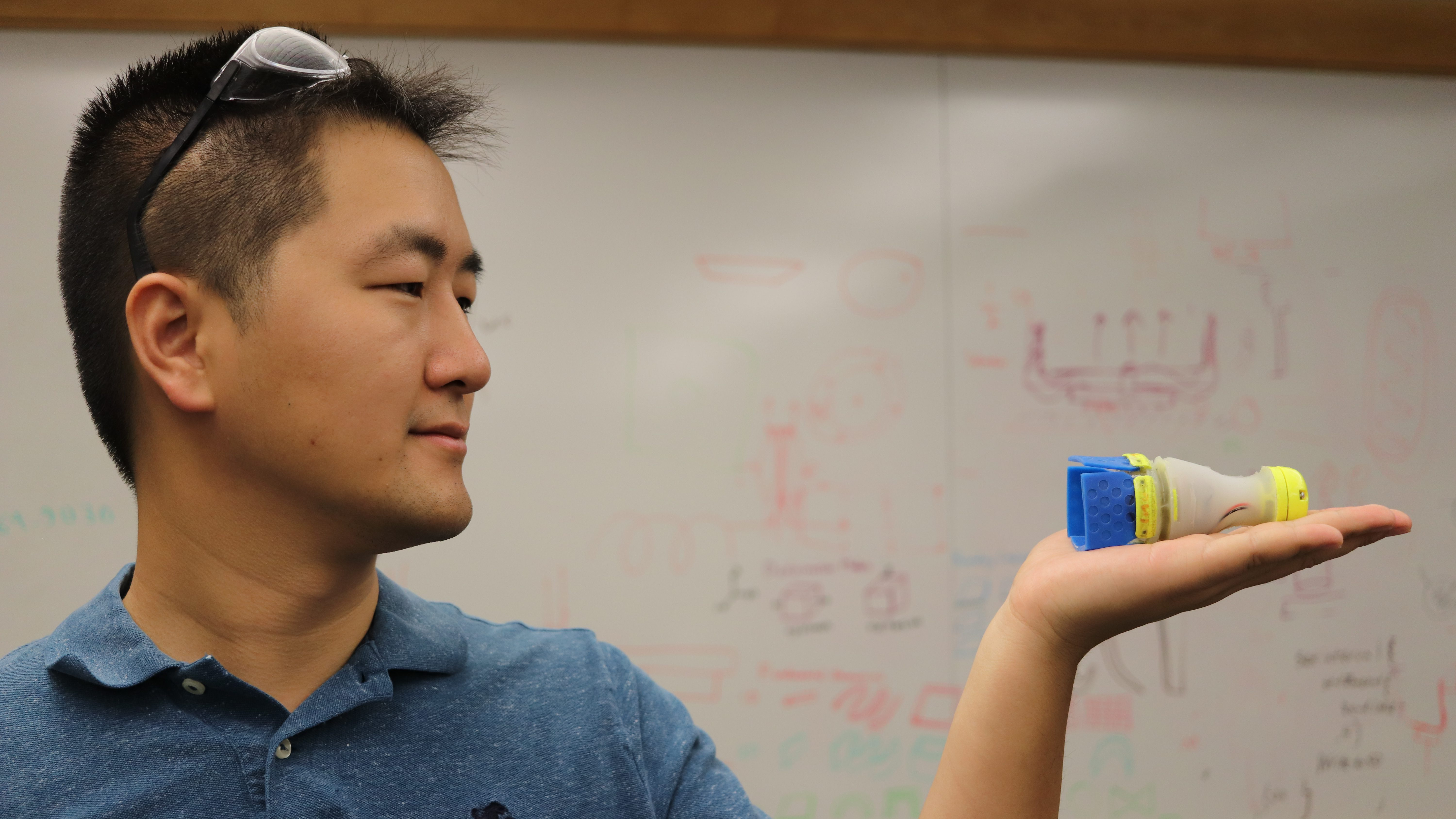 MIT PhD student You Wu holds his invention Robot Daisy in his hand.