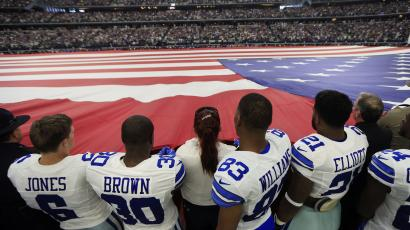 football players hold horizontal US flag during the National Anthem