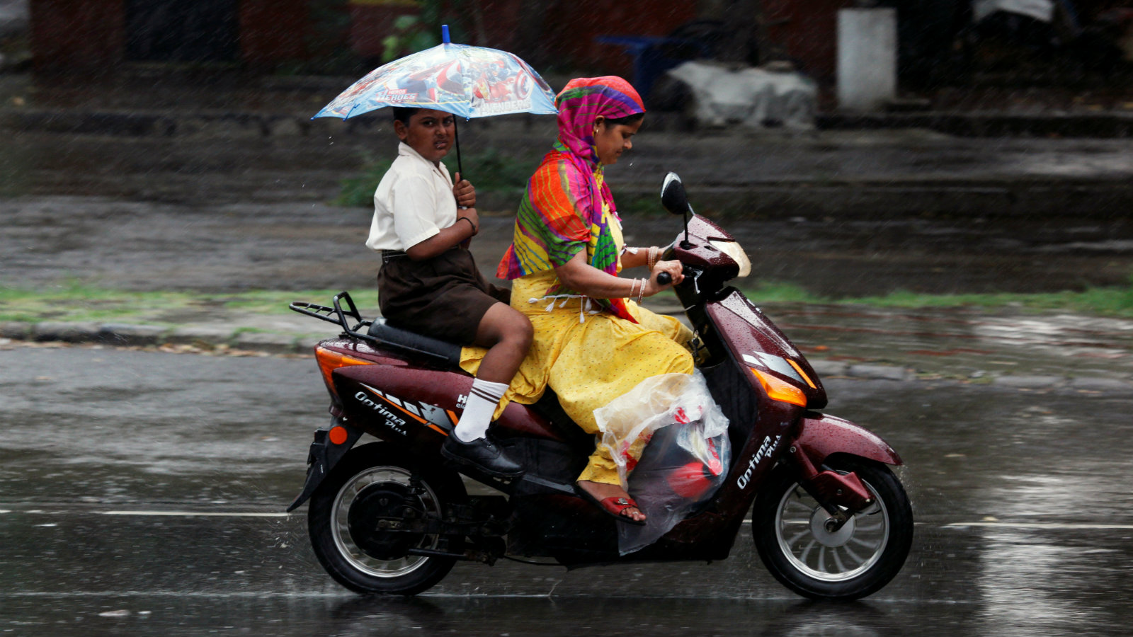 A boy holds an umbrella as he travels on a scooter with his mother during rains in Chandigarh, India, July 14, 2016.