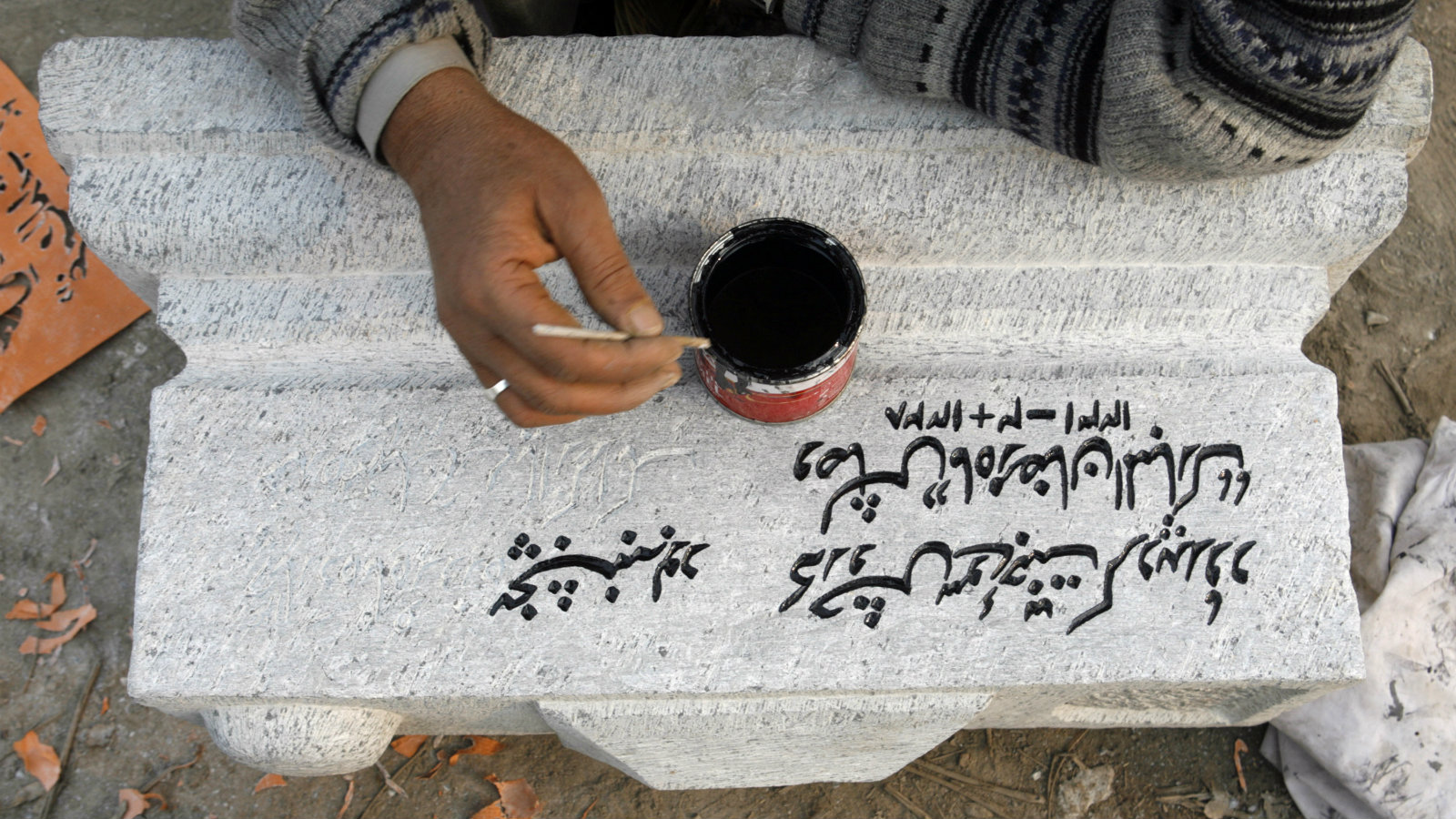 A Kashmiri worker, Ghulam Rasool, writes a Persian couplet on a gravestone at Kashmir's biggest graveyard in downtown Srinagar November 26, 2007.
