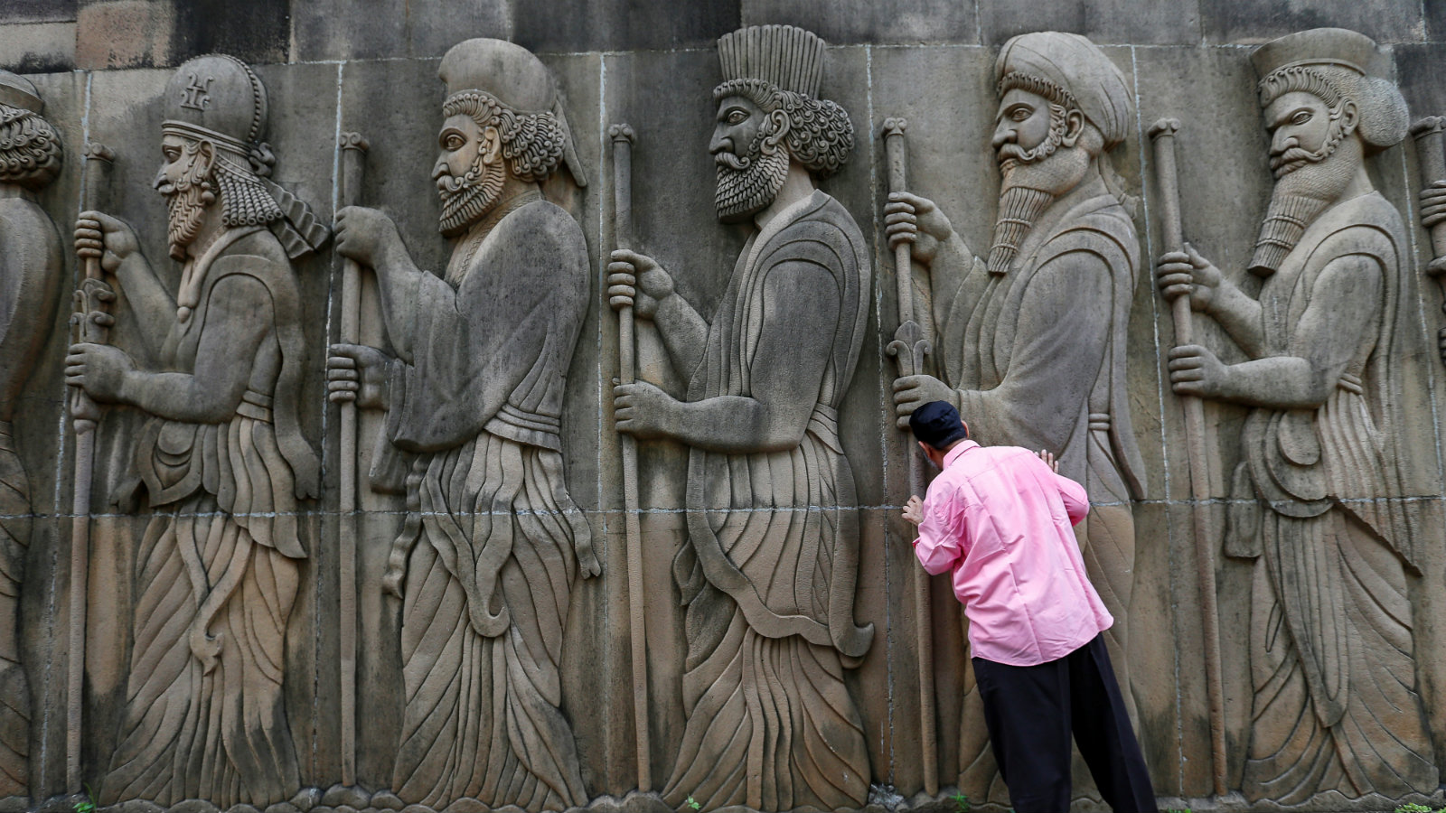 A Parsi man touches the walls of a Parsi fire temple featuring huge carvings of ancient priests during the Parsi New Year day in Mumbai, India, August 17, 2016.