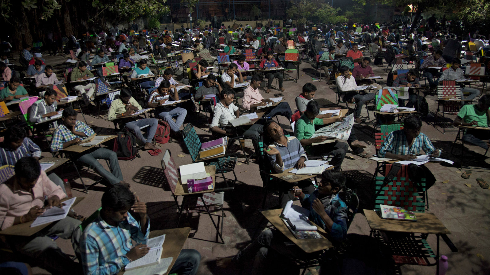 In this Thursday, Feb. 16, 2017 photo, hundreds of Indian college students and job-seekers study in an open ground outside the City Central Library in Hyderabad, India. The open ground here turns into a giant outdoor classroom every day when hundreds of young college students and job-seekers, armed with their books and other study material sit and prepare for examinations till late at night. Many of them bring their own chairs, which they chain to the outer metal grill of the building overnight. Nowhere is the search for jobs more desperate than in India, where around 13 million young people enter the job market every year.