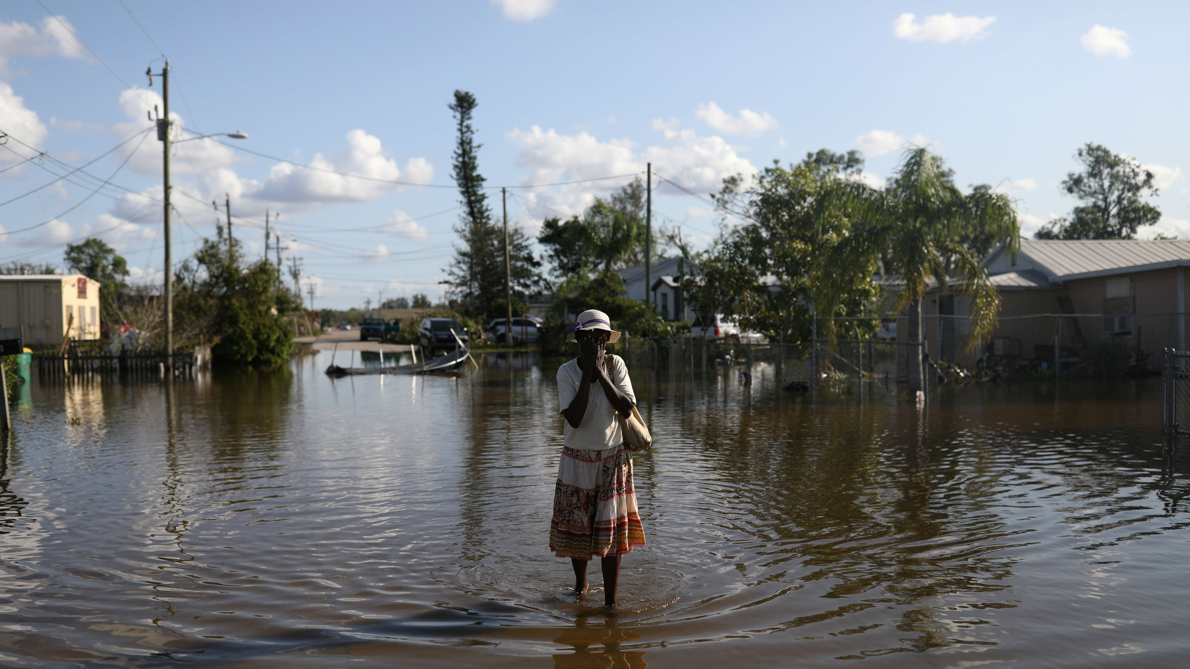 Maria Dorsaint wipes sweat from her face on the way to her church, Haitian United Evangelical Mission, which was damaged by flooding from Hurricane Irma in Immokalee, Florida, U.S. September 12, 2017