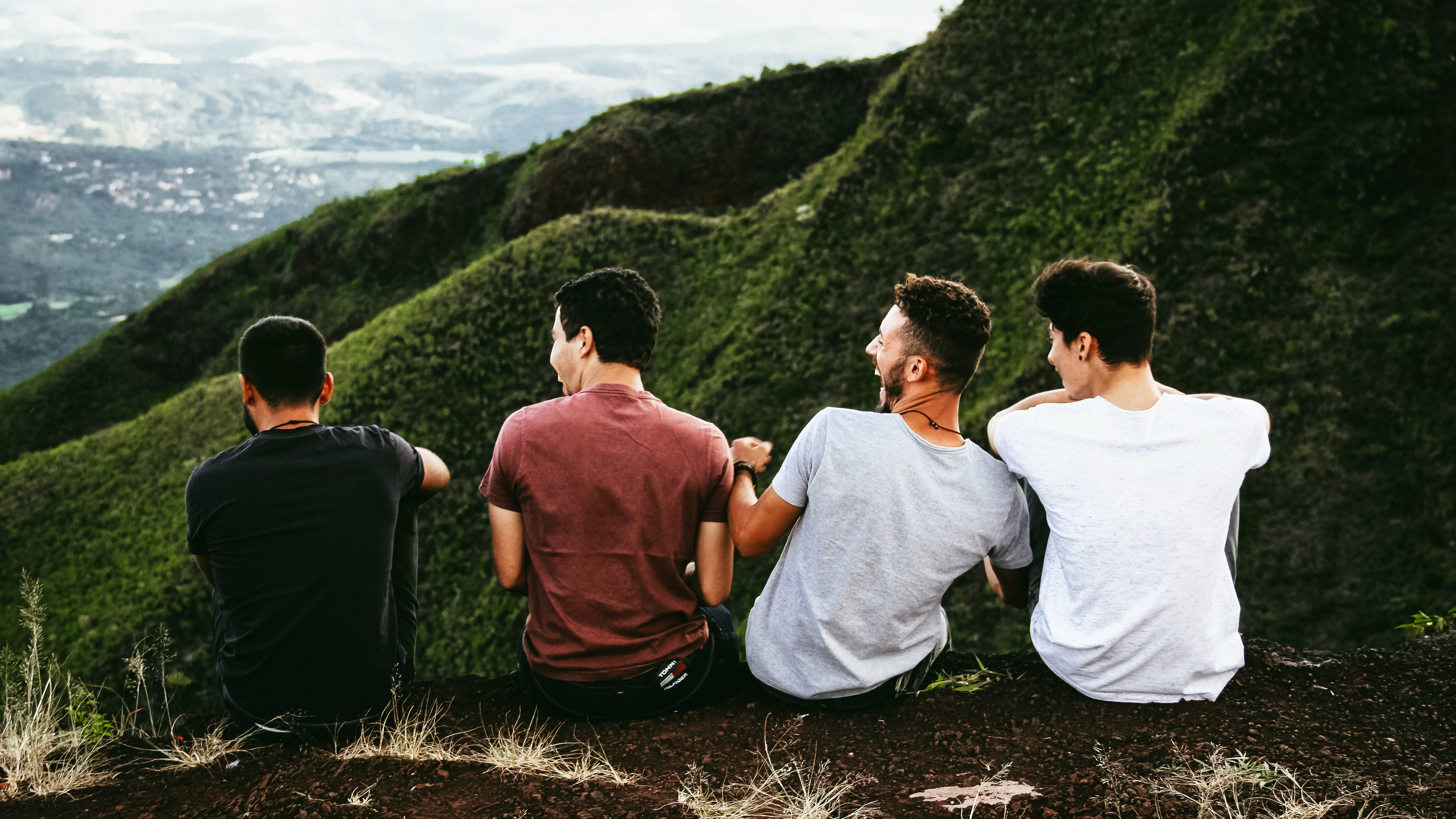 Four boys sitting and laughing.