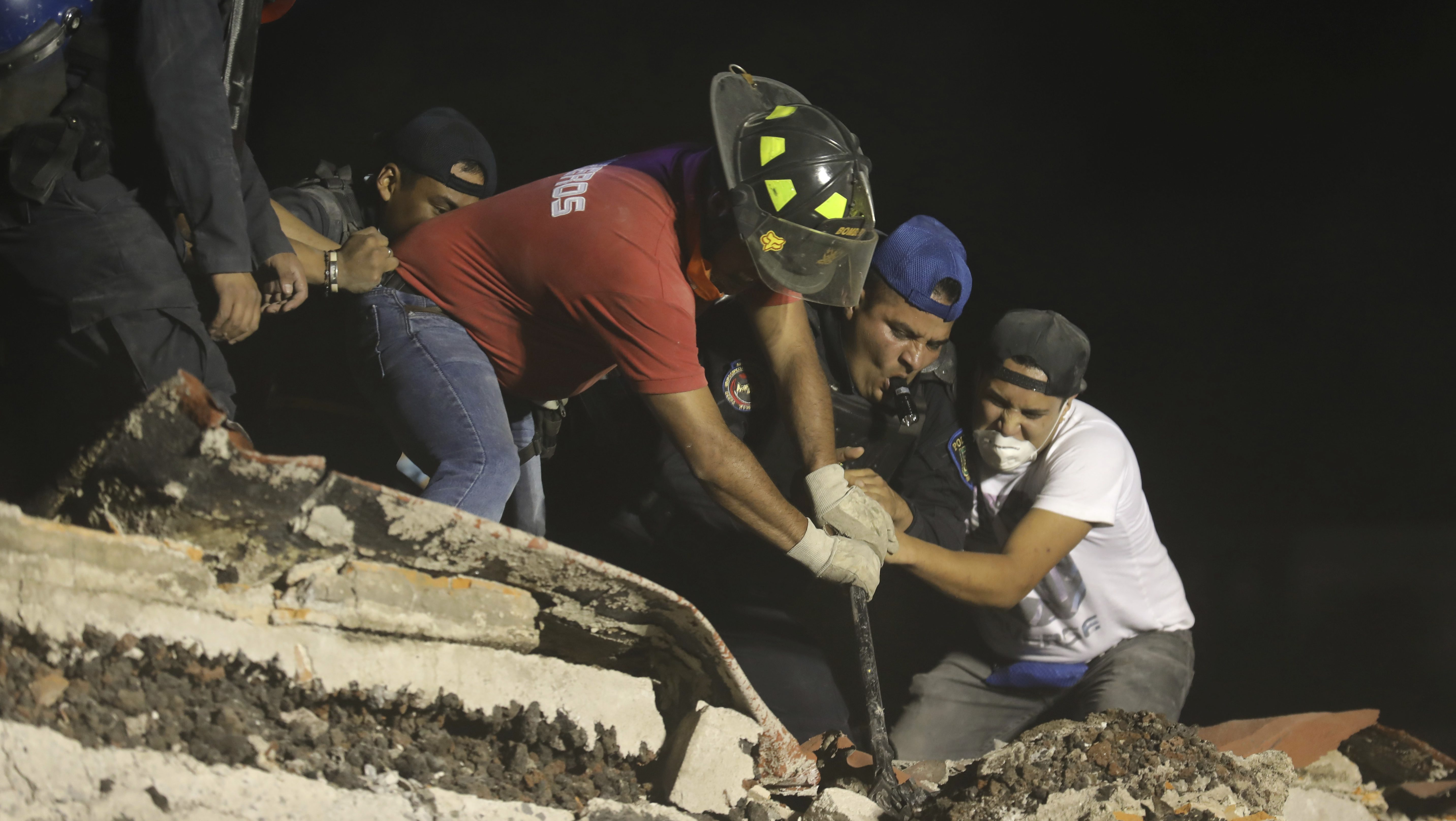 Rescue workers and volunteers search a building that collapsed during Mexico earthquake