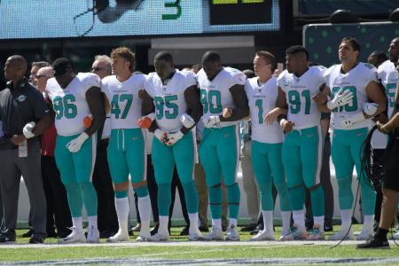 Miami Dolphins players lock arms with teammates during the playing of the national anthem before an NFL football game against the New York Jets