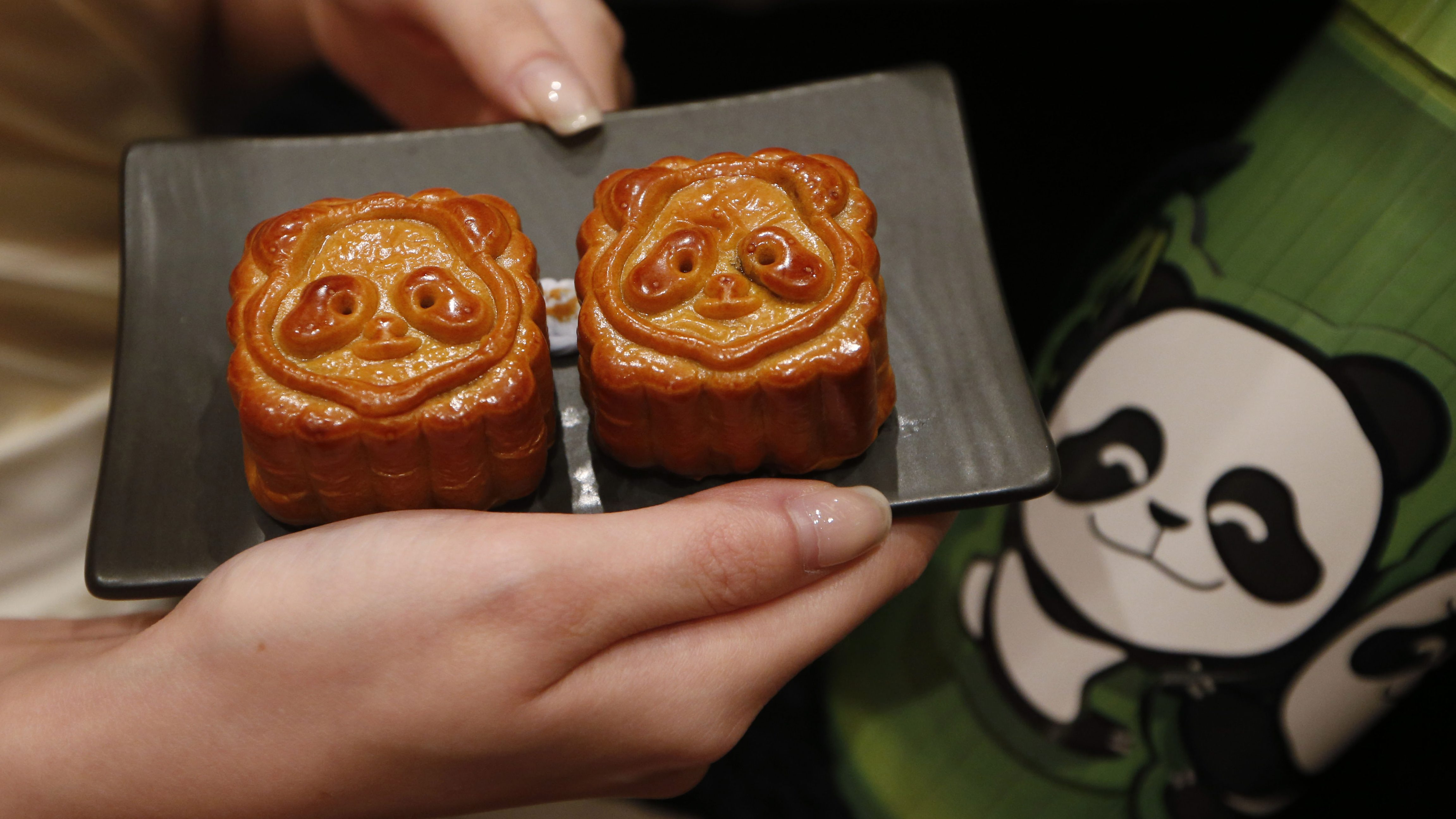 A staff member displays mooncakes glazed with Panda faces part of the celebration of the upcoming Mid-Autumn festival during a media preview of the Food, Tea and Chinese Medicine Fairs in Hong Kong, Wednesday Aug. 1, 2012. More than 1,400 exhibitors from all over the world are expected to participate in the fairs. (AP Photo/Kin Cheung)