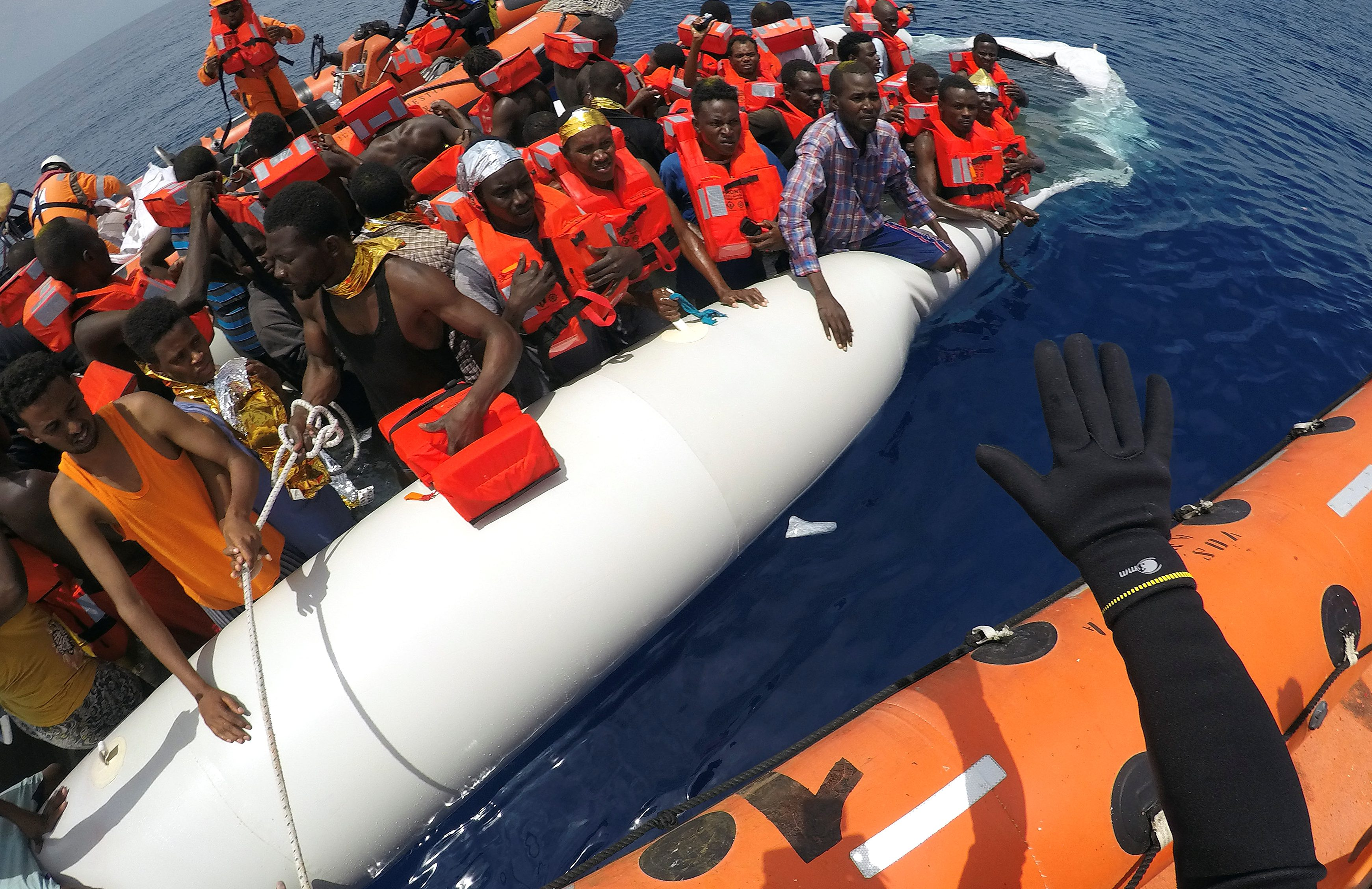 These migrants—on a dinghy to cross the Mediterranean sea from Libya—were rescued in June, 2017. An estimated 2,600 have drowned making the same crossing in unseaworthy ships this year.