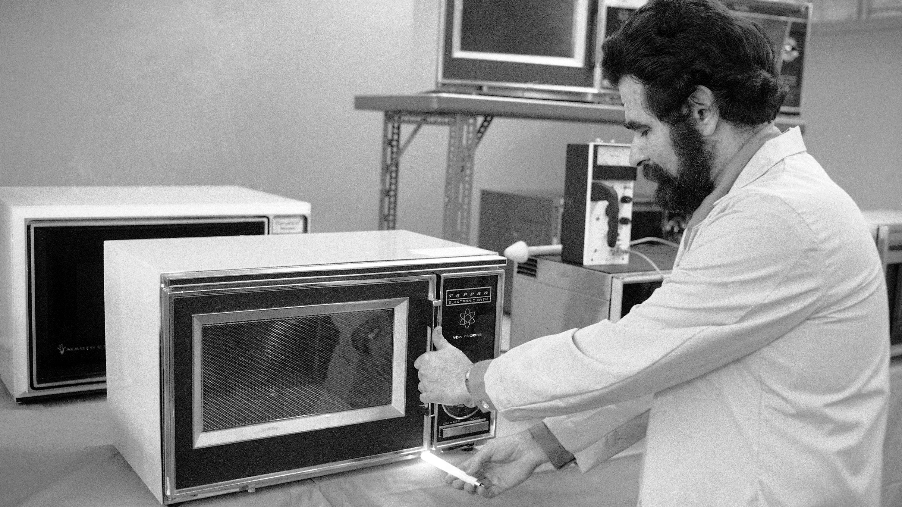 """Allan Eckhaus, consumers union engineer, holds a fluorescent tube near the slightly Ajar Door of a microwave oven, in a demonstration of radiation leakage in the ovens, in Mount Vernon, New York on March 7, 1975. Consumer union released a statement the same day during that consumers should """"be cautious and stay away"""" from buying the ovens, citing evidence of measurable radiation leakage from the 15 most popular brands."""