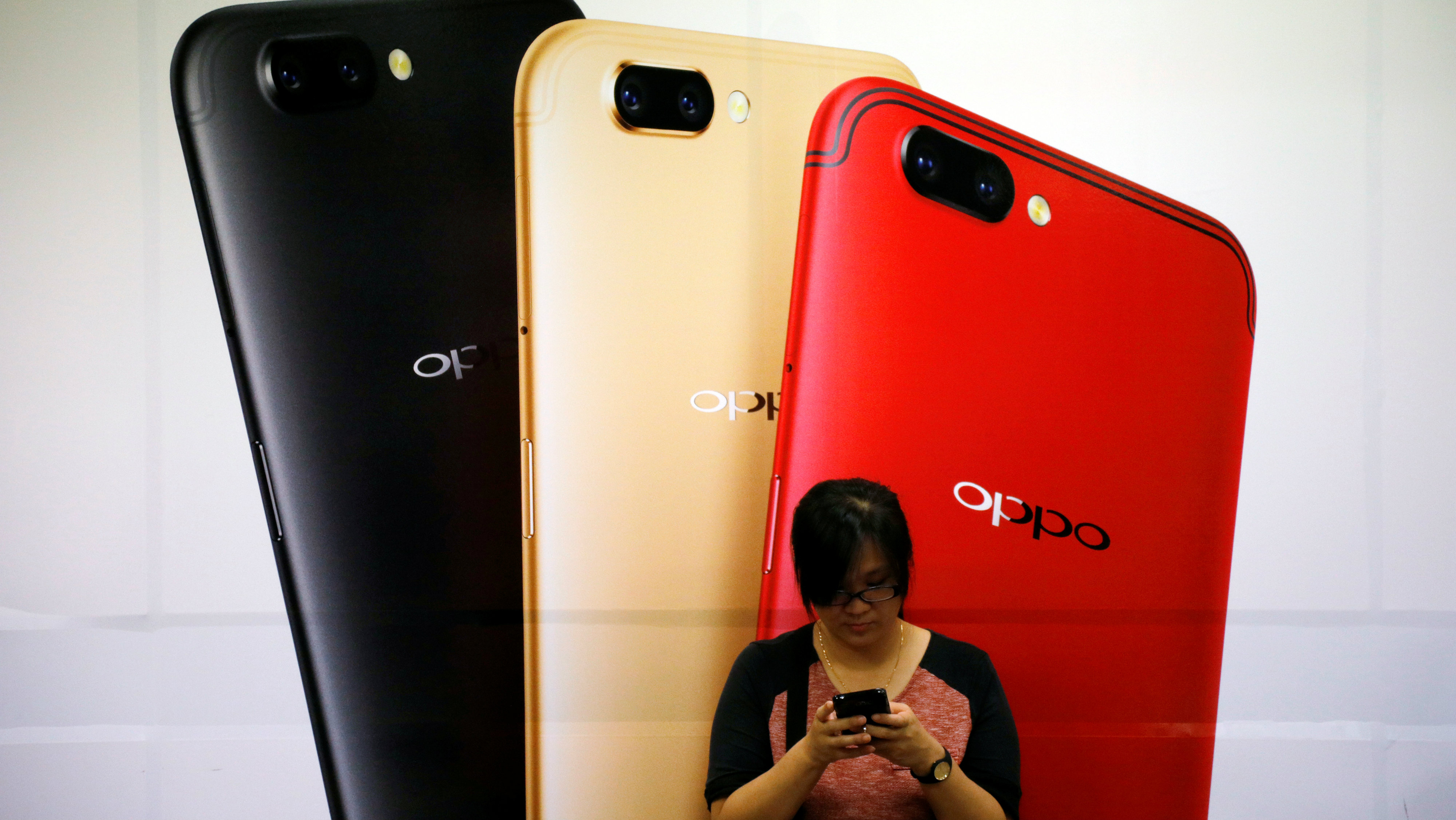 A woman uses her mobile phone next to an Oppo mobile handset advertisement in Singapore August 7, 2017.