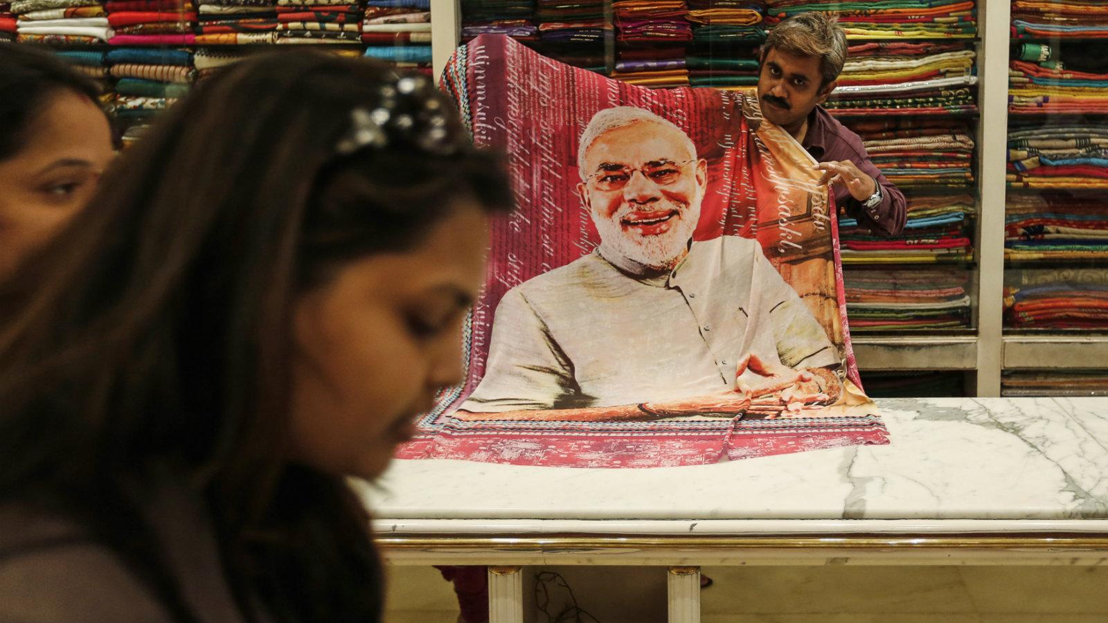 A salesman displays a sari at a showroom in Mumbai.