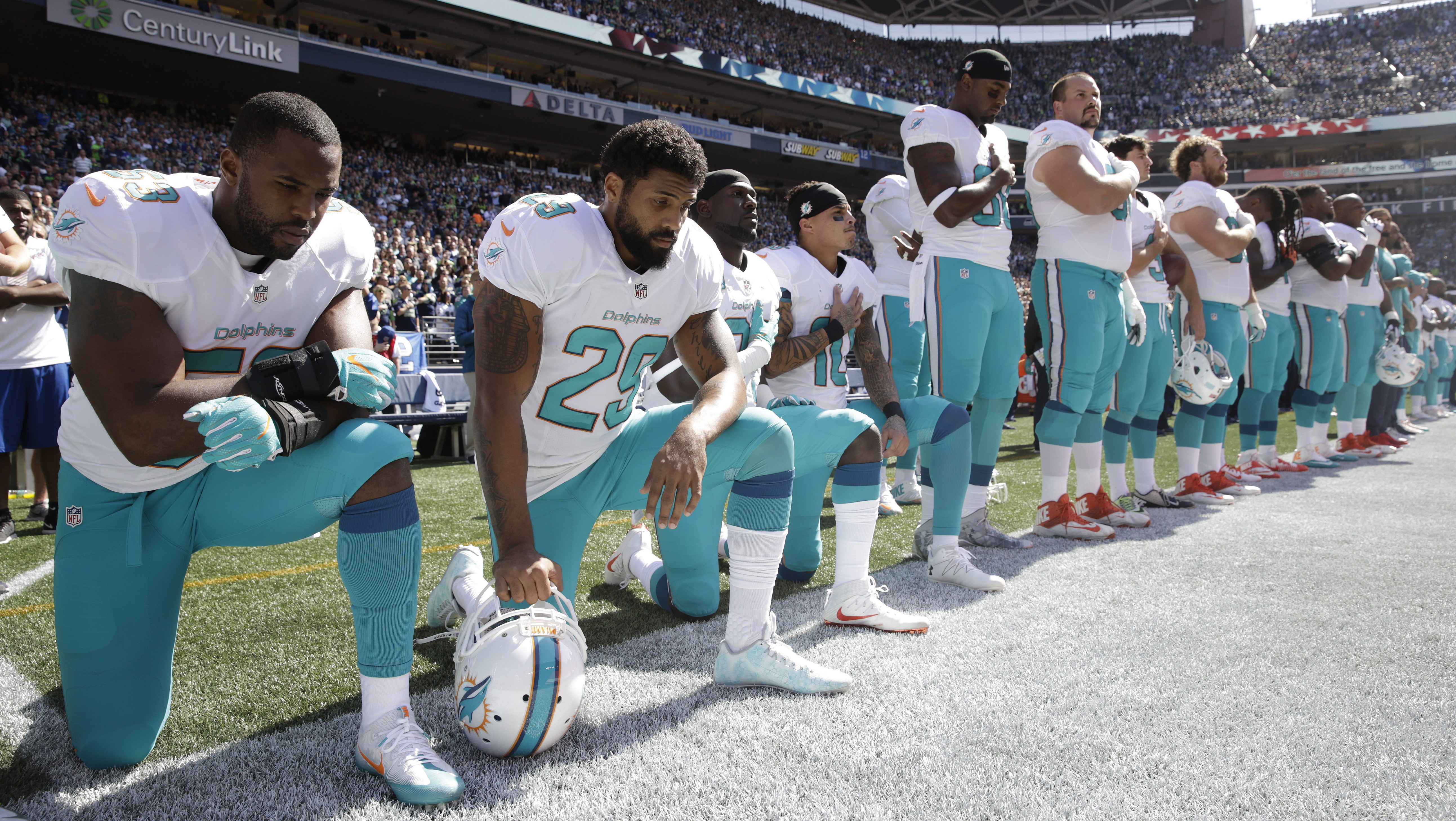Miami Dolphins' players kneel during the singing of the national anthem