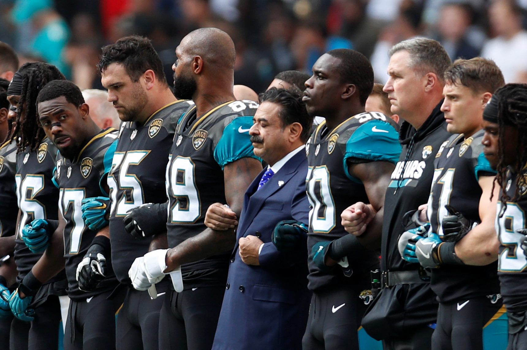 Jacksonville Jaguars owner Shahid Khan links arms with players during the national anthems before the match with Baltimore Ravens