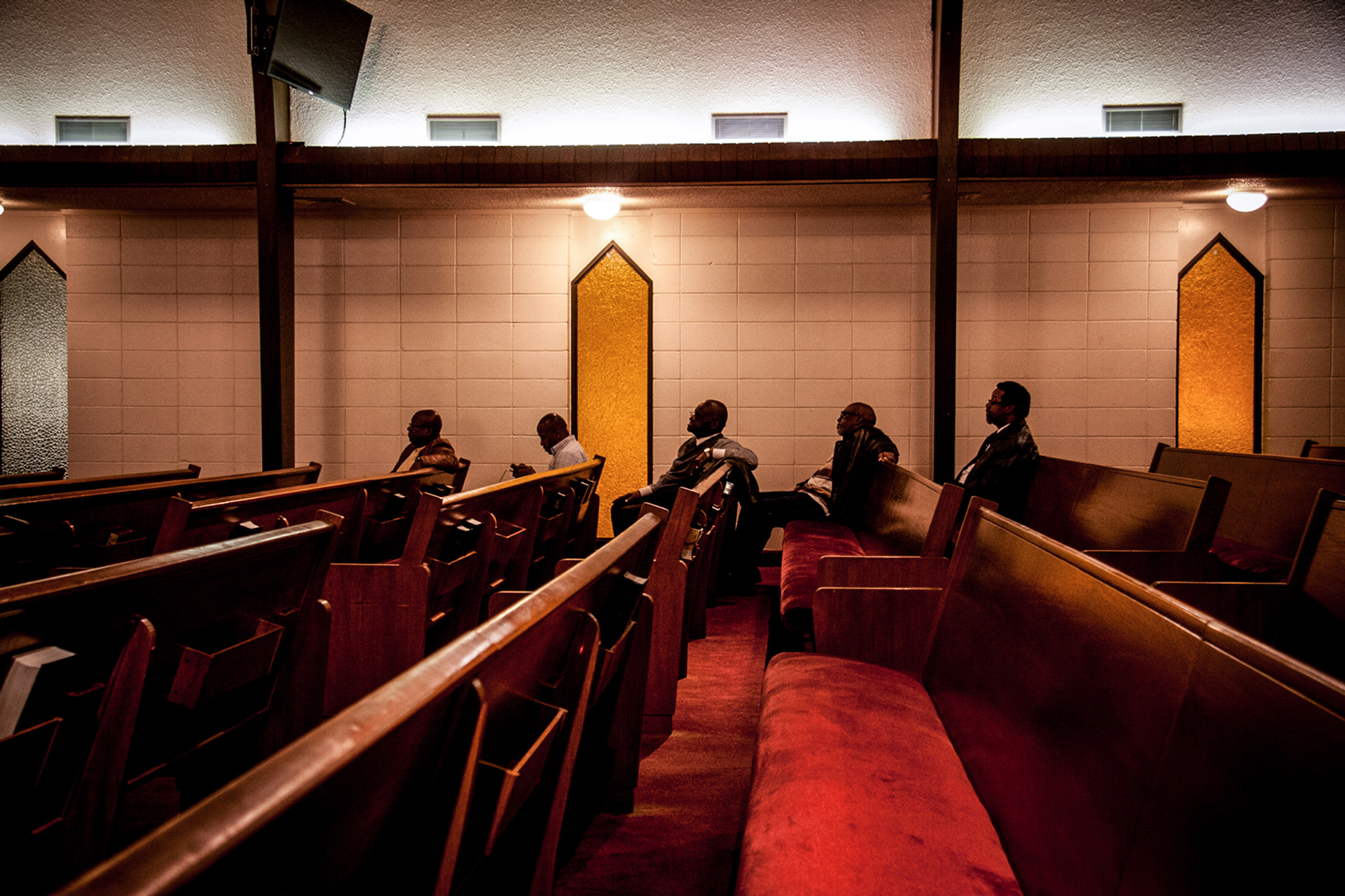 Five men sit listening to their family and friends sing in the 12th District Mass Choir at the Bethel A.M.E. Church, in Little Rock, Arkansas, 2015.
