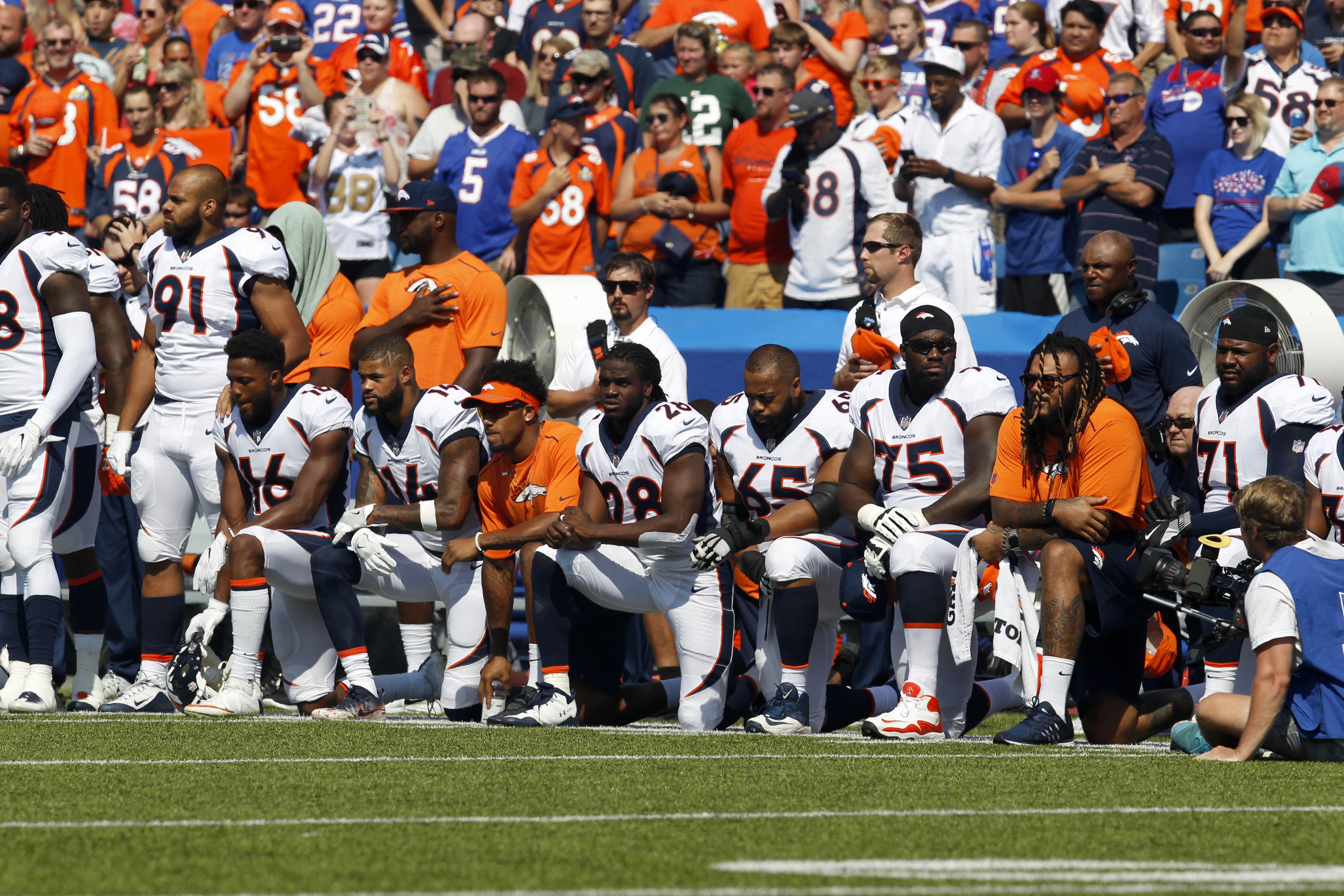 Denver Bronco players kneel in protest during the National Anthem before a game against the Buffalo Bills