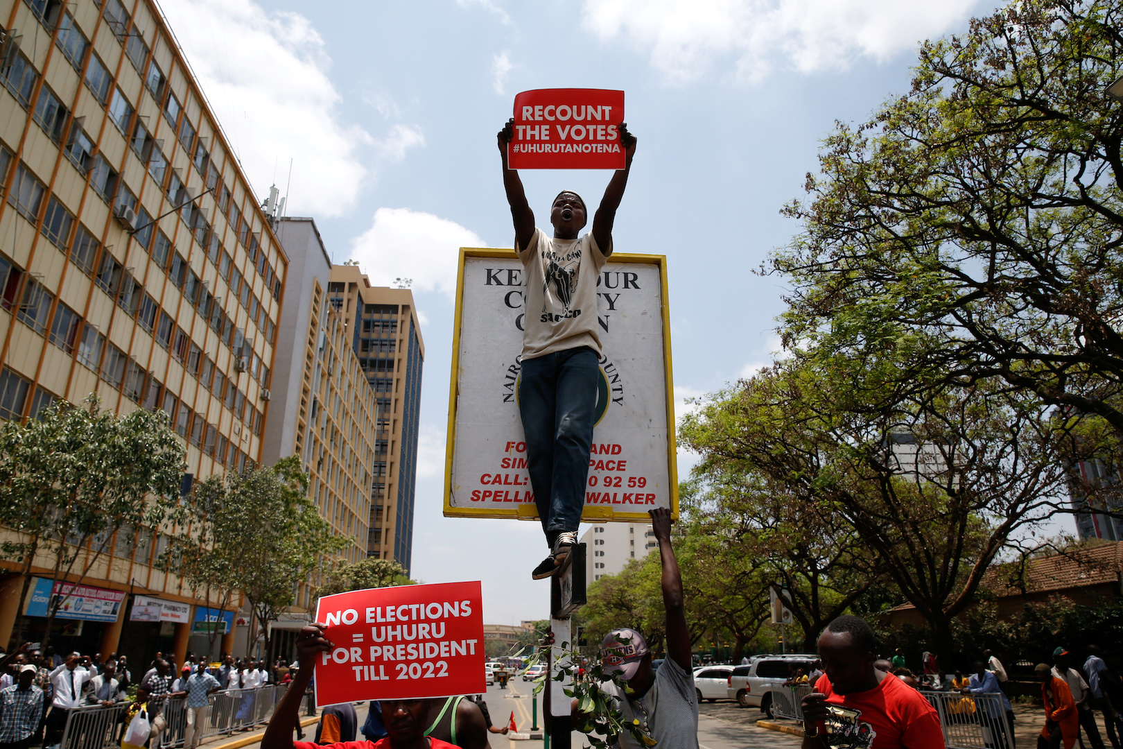 A supporter of Kenya's President Uhuru Kenyatta carries a placard as they demonstrate outside the Supreme Court in protest of the nullification of Kenyattaís victory by the Supreme Court Judges in Nairobi, Kenya, September 19, 2017.