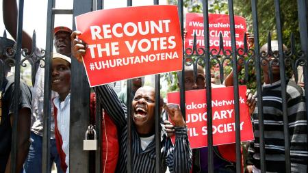 Supporters of Kenya's President Uhuru Kenyatta carry placards as they demonstrate outside the Supreme Court in protest of the nullification of Kenyattaís victory by the Supreme Court Judges in Nairobi, Kenya, September 19, 2017.