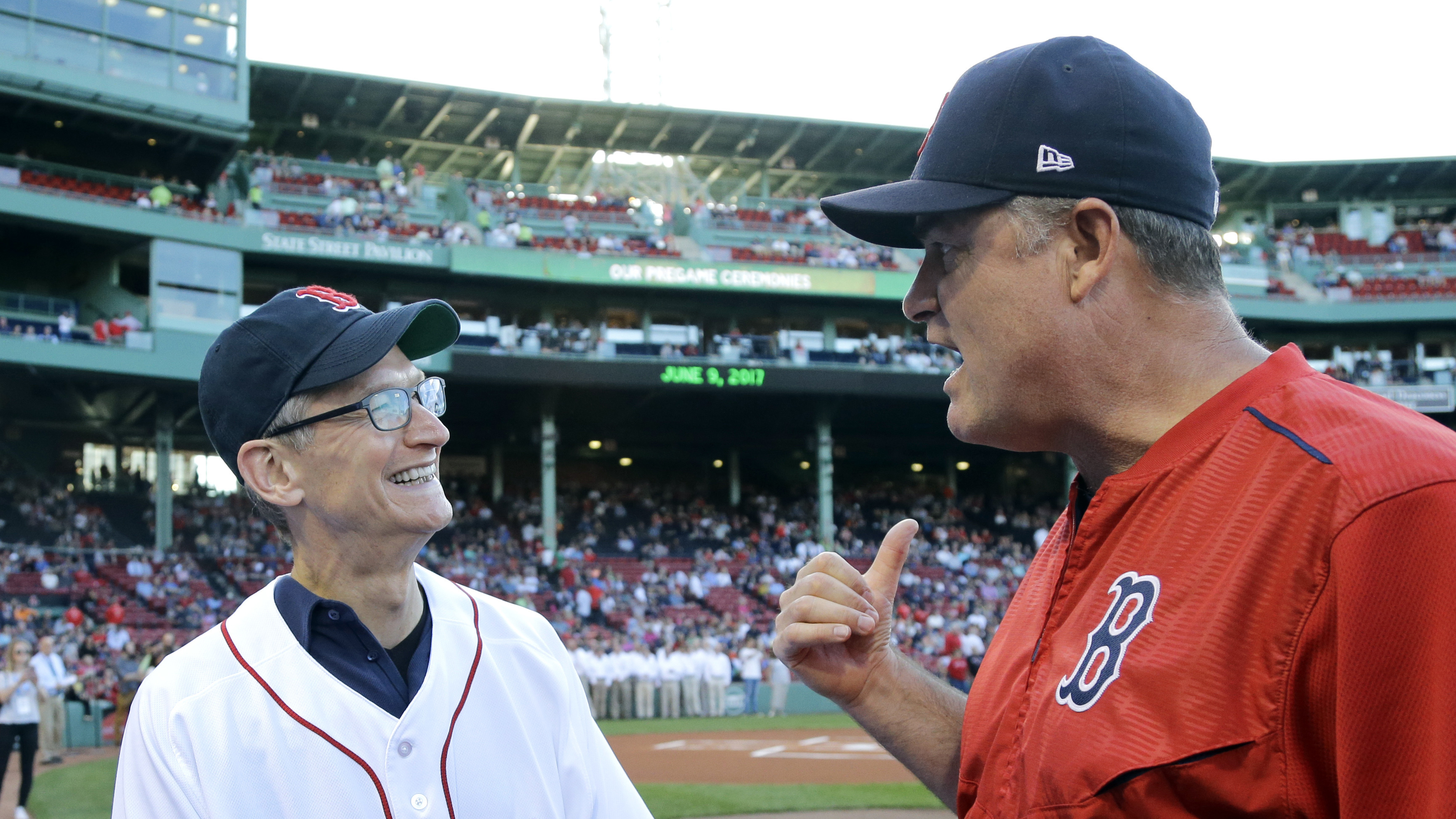 Apple CEO Tim Cook, left, chats with Boston Red Sox manager John Farrell before the Red Sox's baseball game against the Detroit Tigers at Fenway Park, Friday, June 9, 2017, in Boston. (AP Photo/Elise Amendola)
